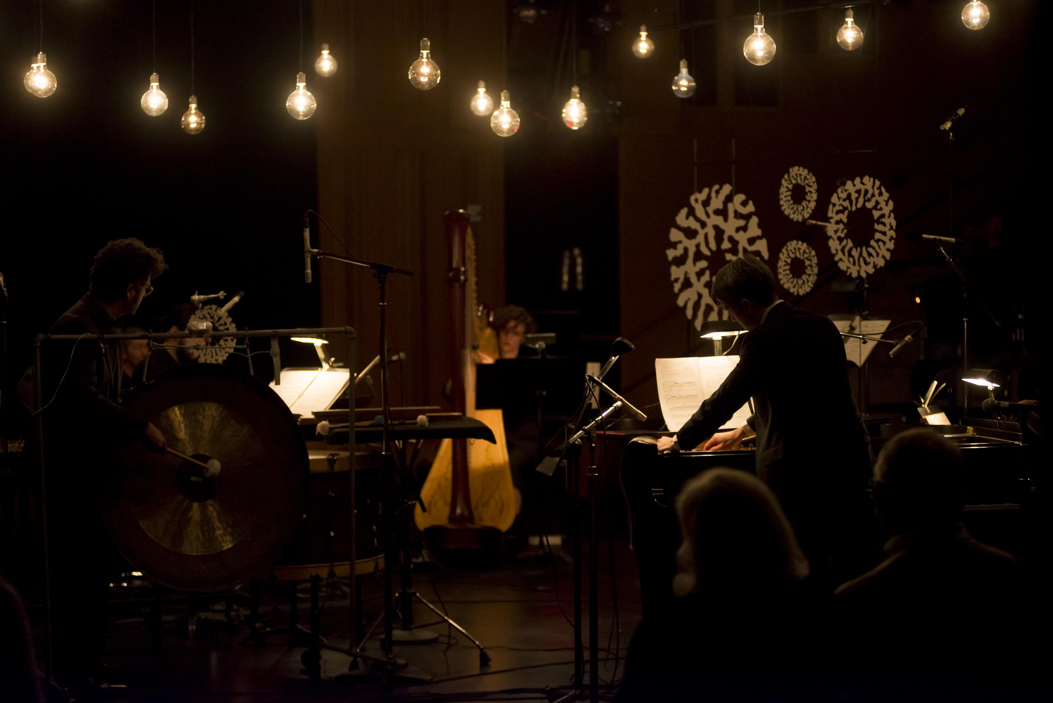 A dark room is lit by a suspended string of light bulbs hanging above performing musicians.