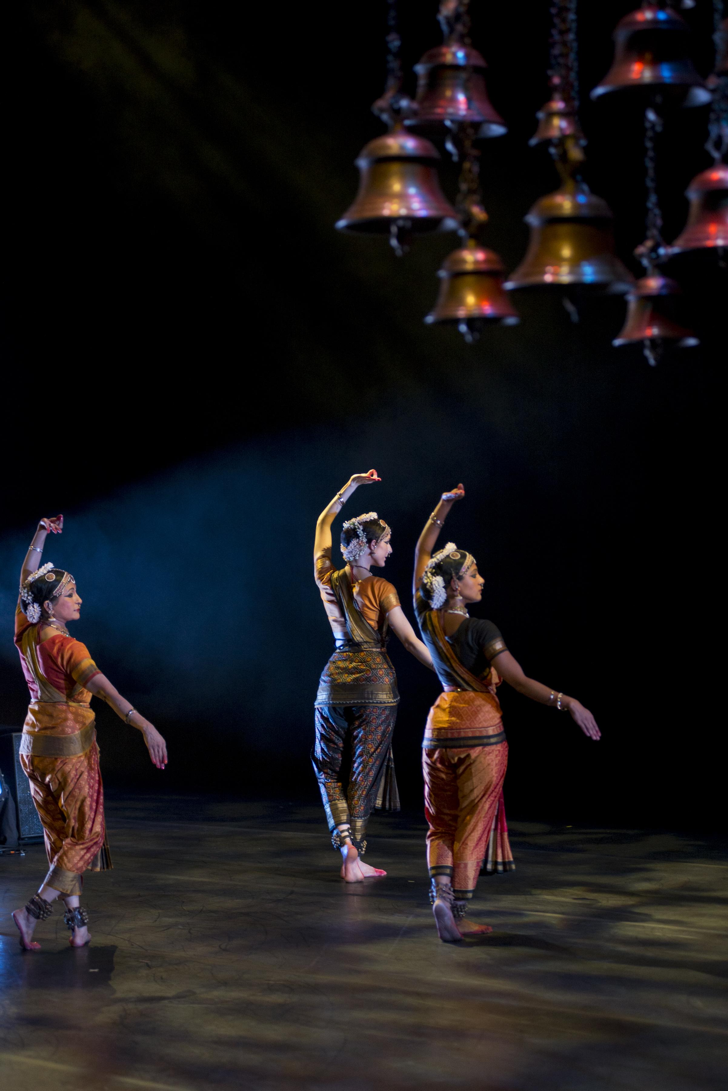 Three women wearing Indian saris, jewelry, and head ornaments dance in unison on a bare stage beneath hanging brass bells.