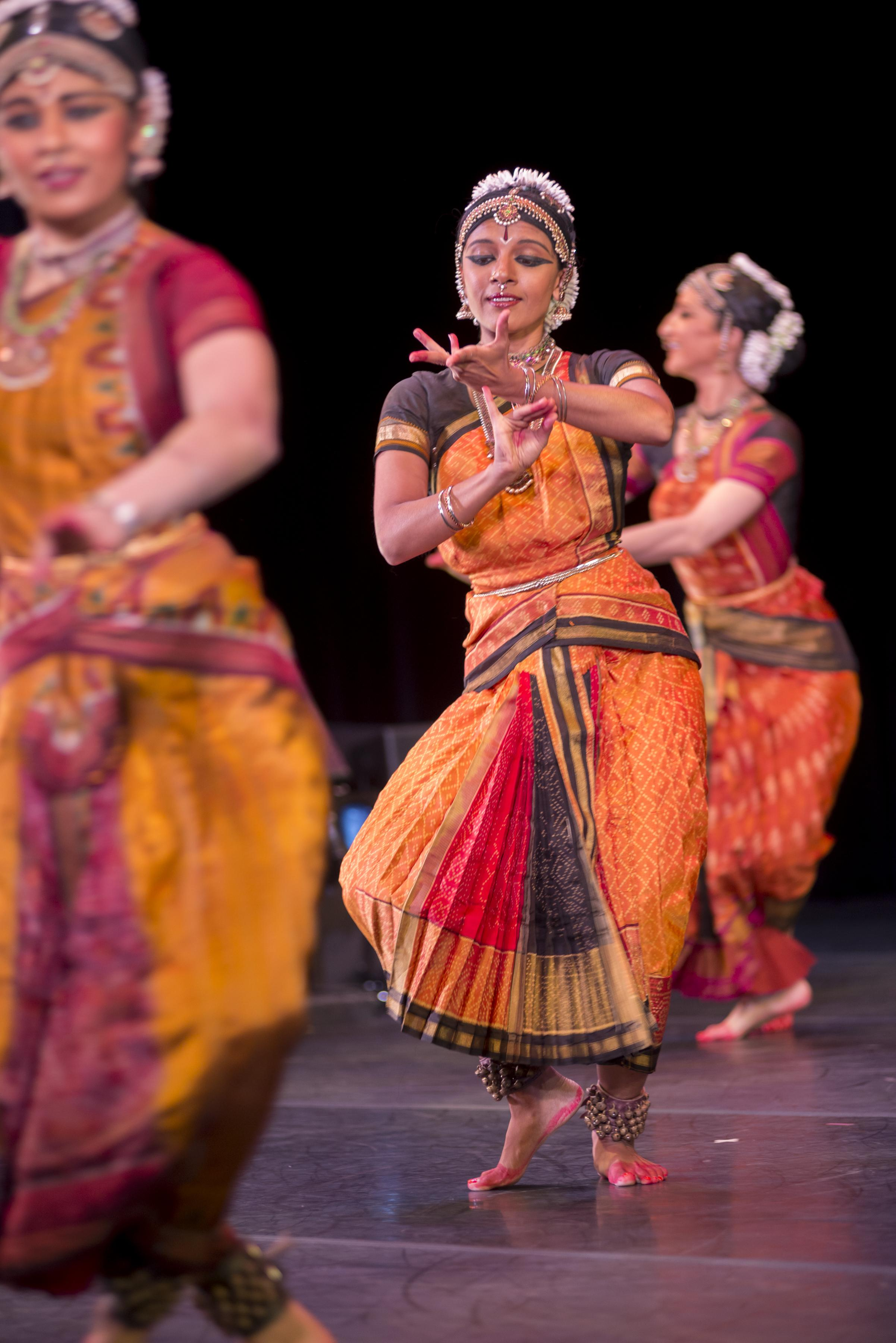 Three women on stage wearing Indian saris, elaborate head pieces, and jewelry, dance barefoot on a stage with arms bent and fingers flexed.