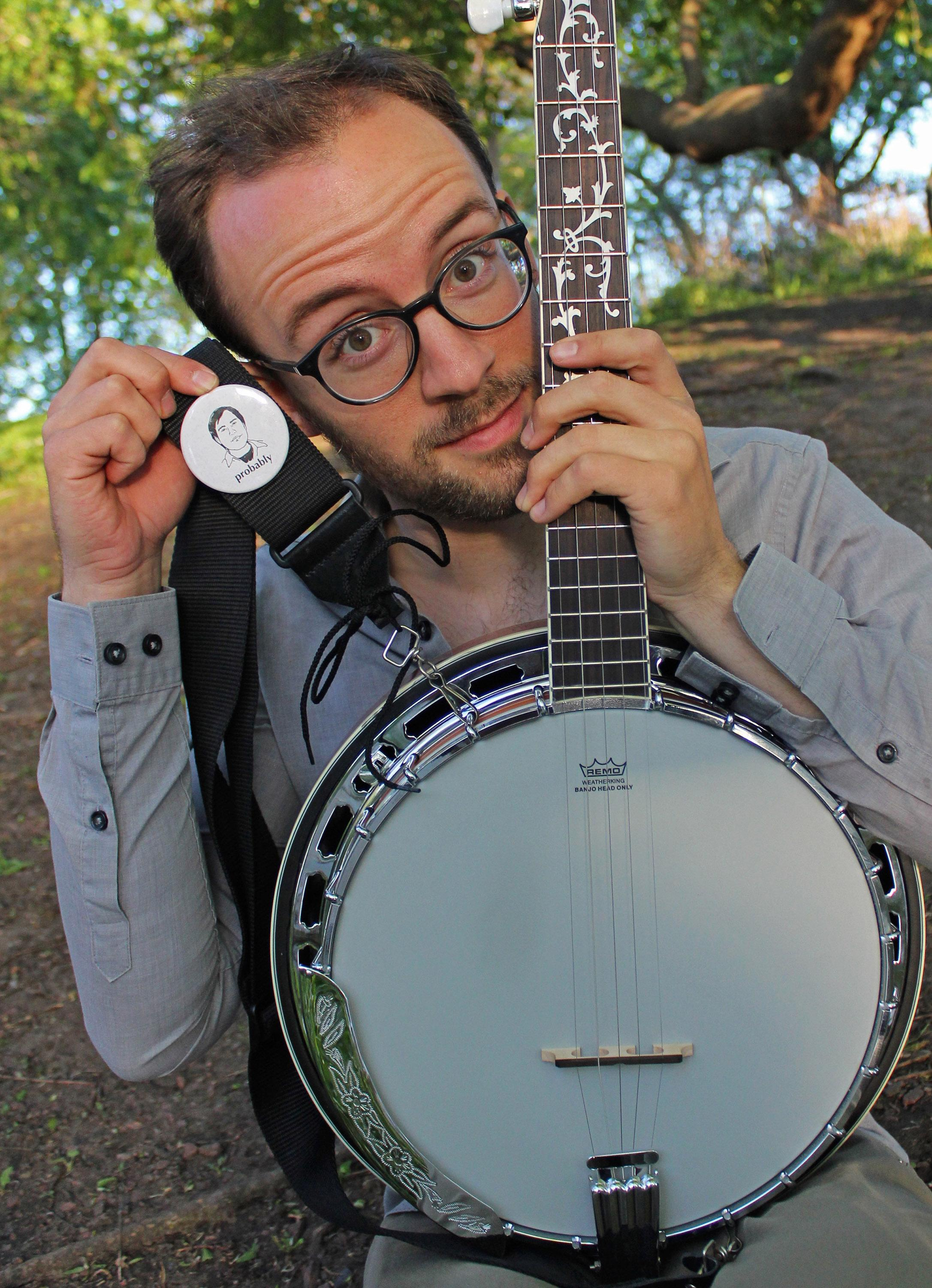 """A young man with round glasses and facial hair holds the neck of a bango near his face with one hand while holding a white badge with an image of a face and the word """"Probably"""" in an outdoor wooded setting."""