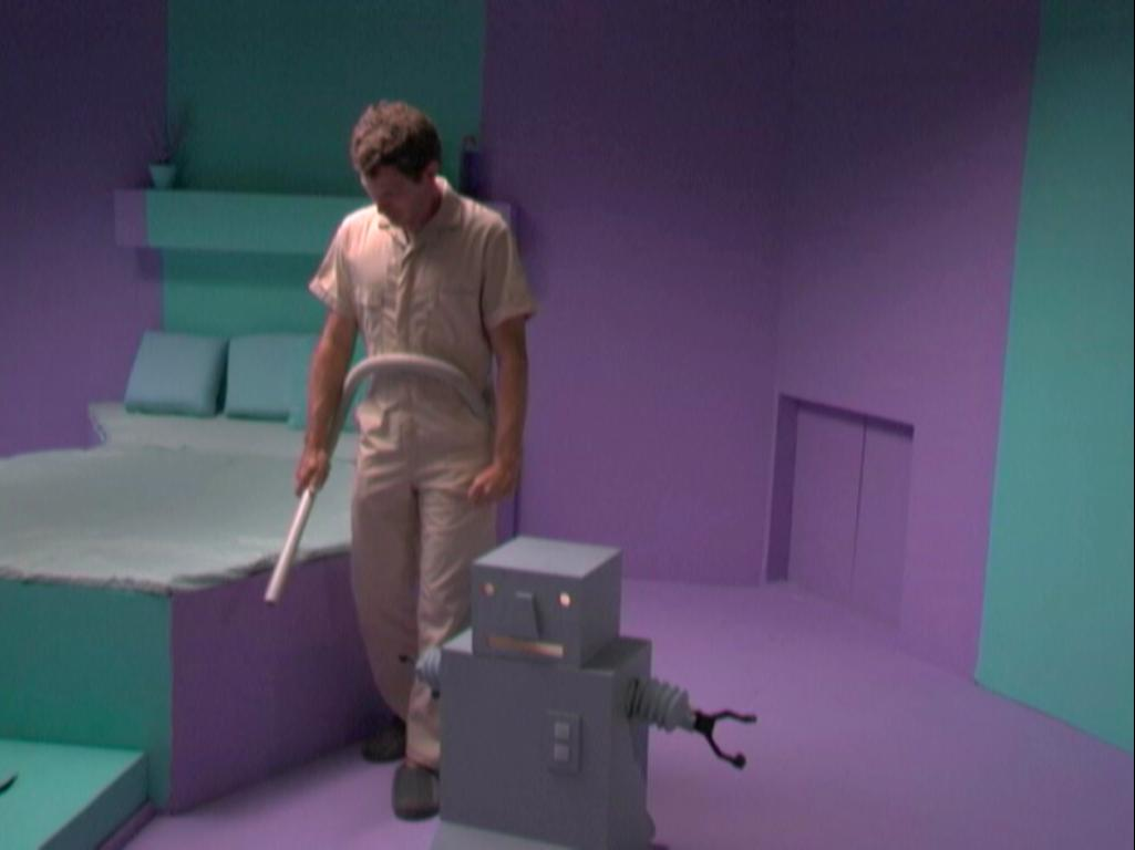 Film still of a man in a khaki jumpsuit and a grey, cubic robot in a purple and teal futuristic bedroom