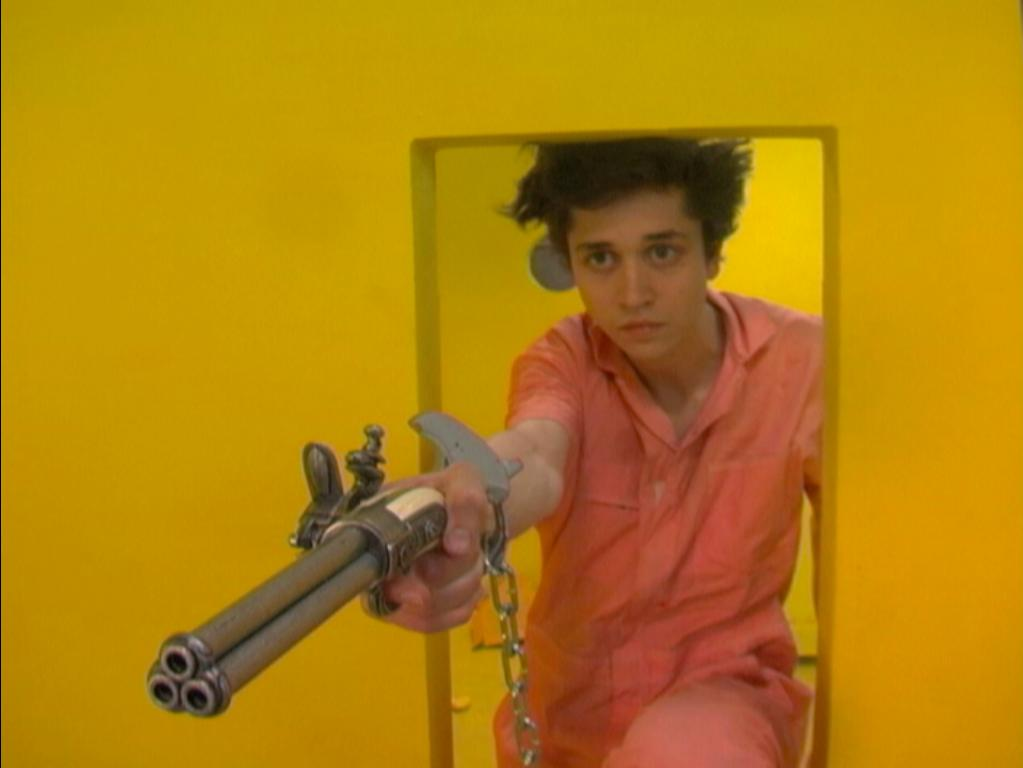 Film still of a person wearing a peach jumpsuit and one handcuff crouching in the small doorway of a mustard yellow room and aiming a three barrel gun to the left of the camera