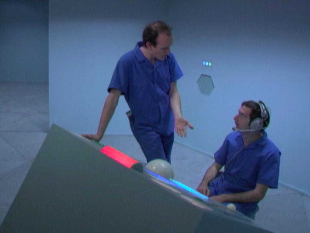 Film still of two men, one standing and one seated, dressed in blue jumpsuits talking near a futuristic console