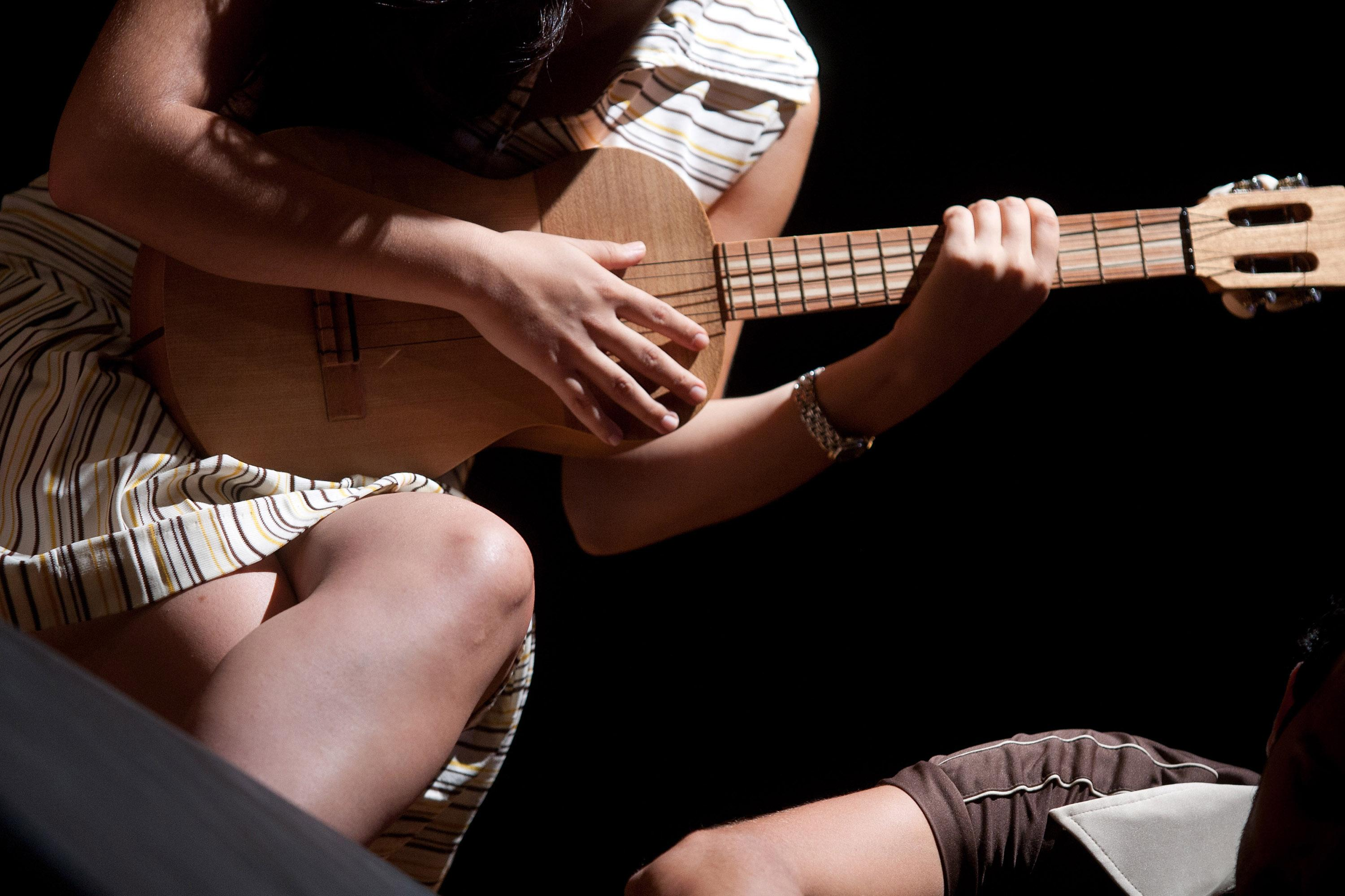 Closely cropped photograph of a seated person wearing a dress, their head off-camera, legs crossed at the knee, cradling a small guitar in a dark space. The upper right arm of an additional person appears at the bottom-righthand corner of the image.