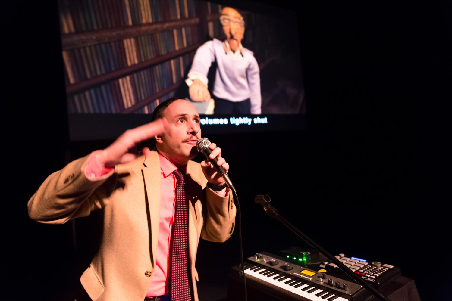 A man in a suit and tie stands near an electronic keyboard, gesturing with one hand and holding a microphone in the other. A video of an old man is projected in the background.