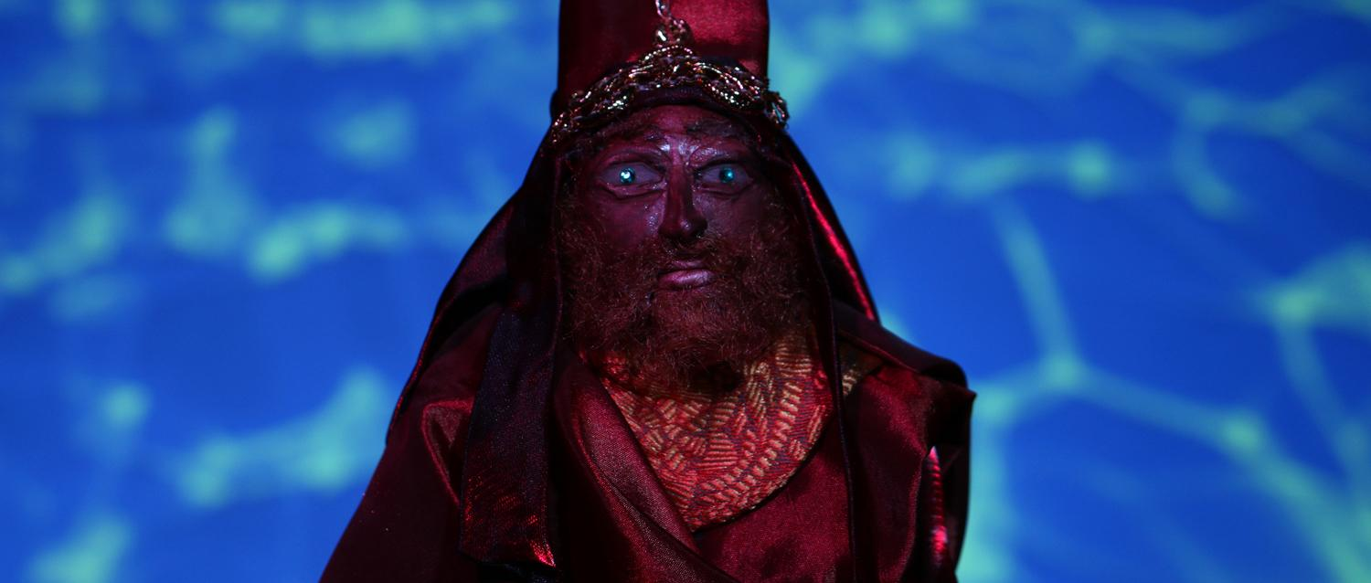 Bearded red human puppet wearing an ornamental outfit against a blue patterened background