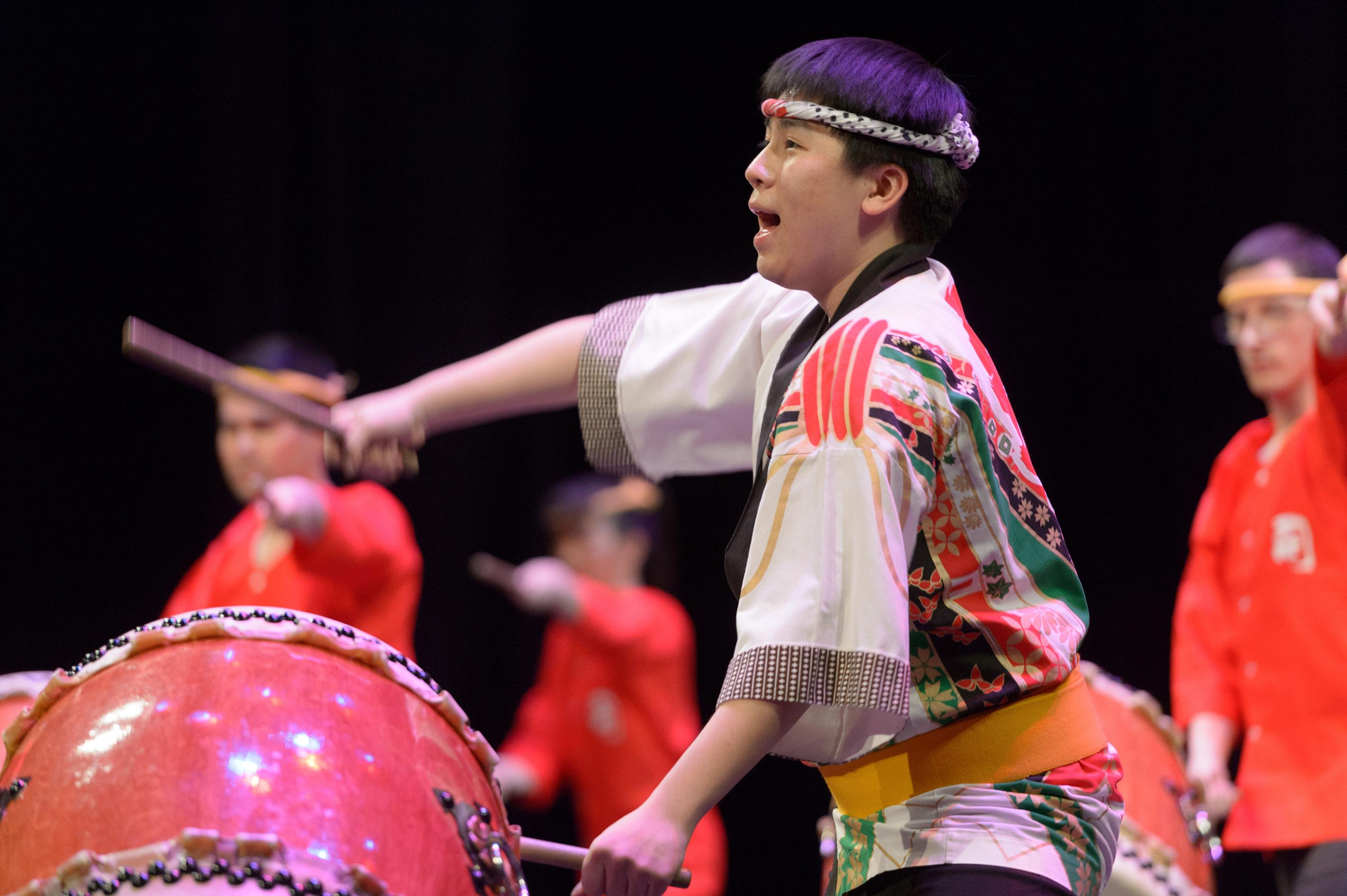 A man wearing a head band and traditional Japanese dress strikes a drum while singing.
