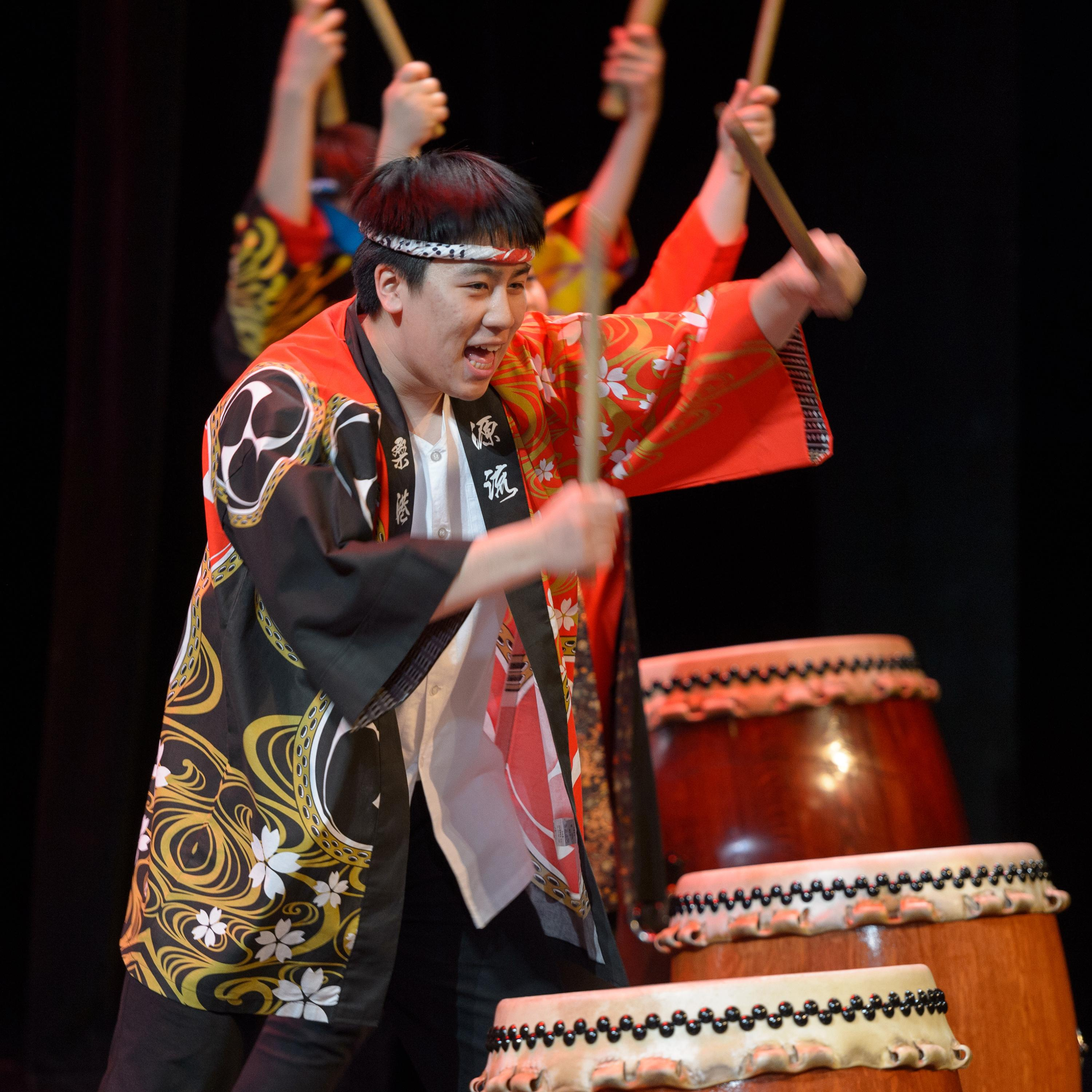 Performance still of a retreating line of drummers holding their sticks above Japanese *taiko* drums