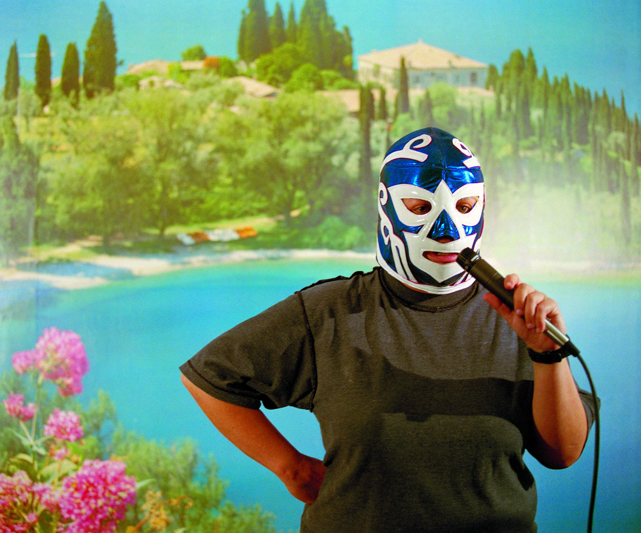 Against a tropical backdrop, a person in a blue-and-white wrestling mask holds a microphone up to their mouth.