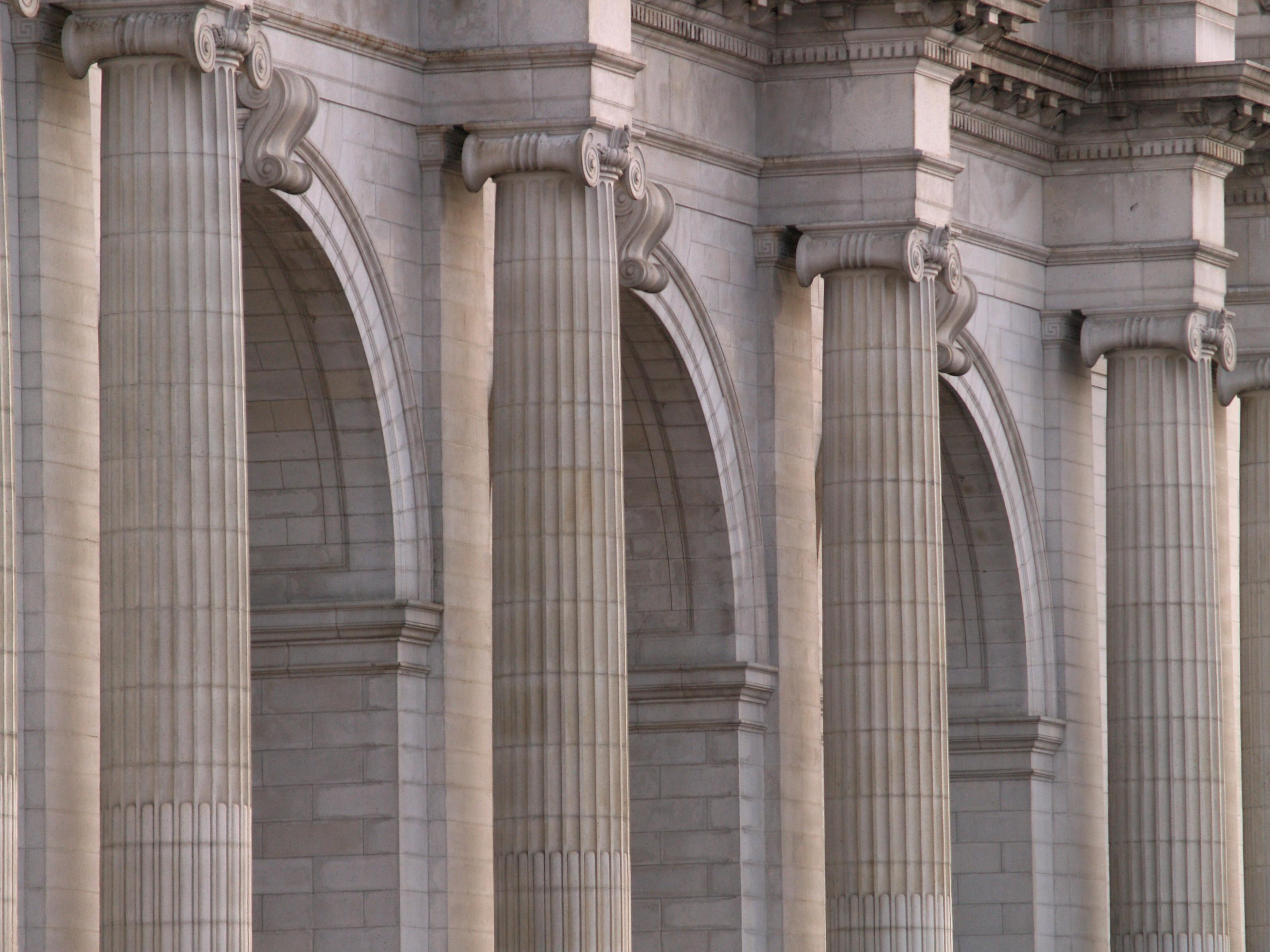 A row of four ionic columns frame three arches.