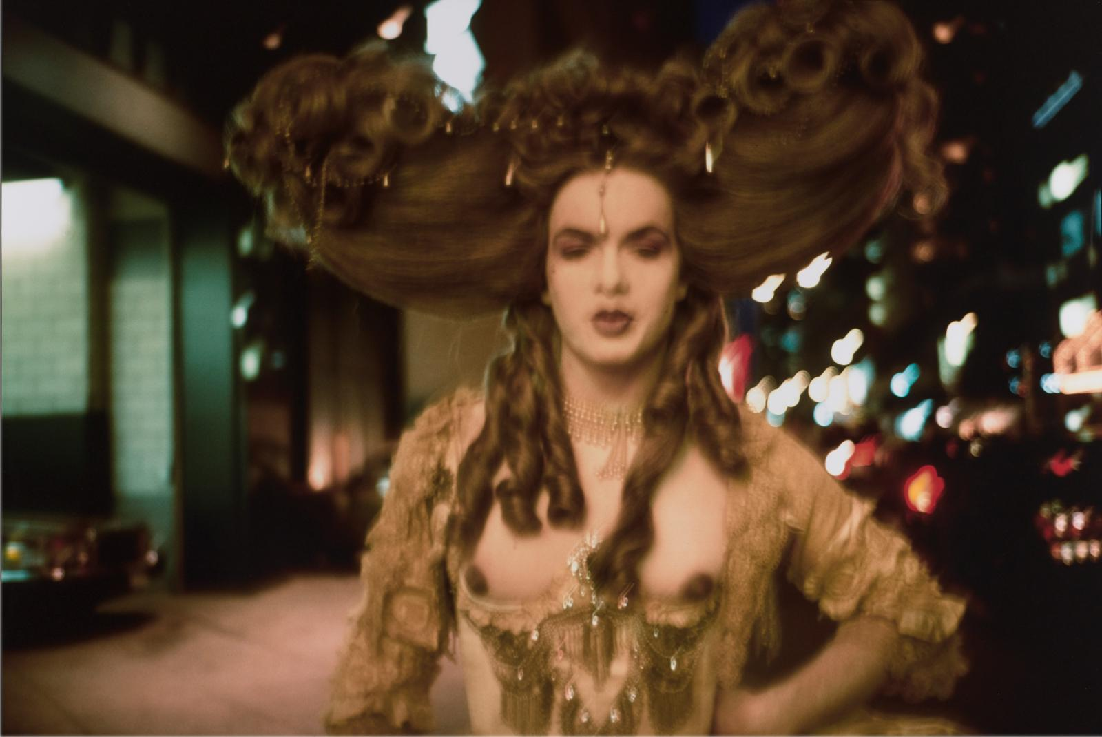 A blurry image shows a light-skinned feminine person with an elaborate updo, corkscrew curls, and a made-up face on a city street at night, posing left hand on hip and wearing a lacy, bejeweled dress with a deep neckline that exposes dark nipples.