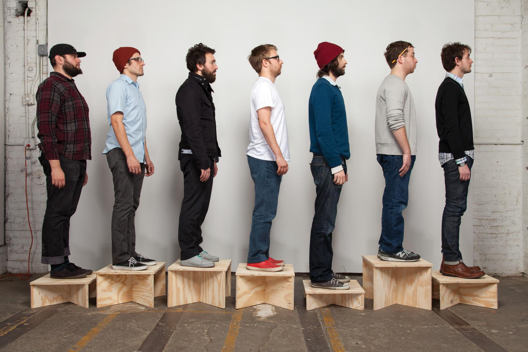 Seven light-skinned people stand in a line, facing toward your right. They are standing on various sized wooden boxes.