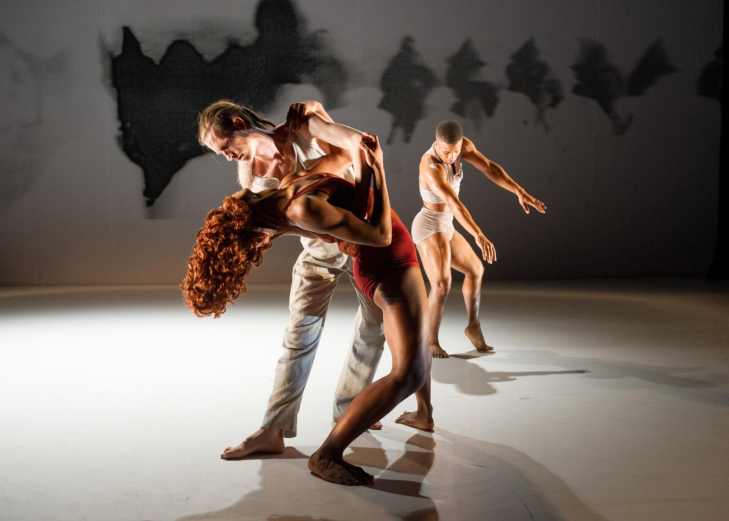 Video still of three dancers with torqued bodies on a dramatically lit stage.