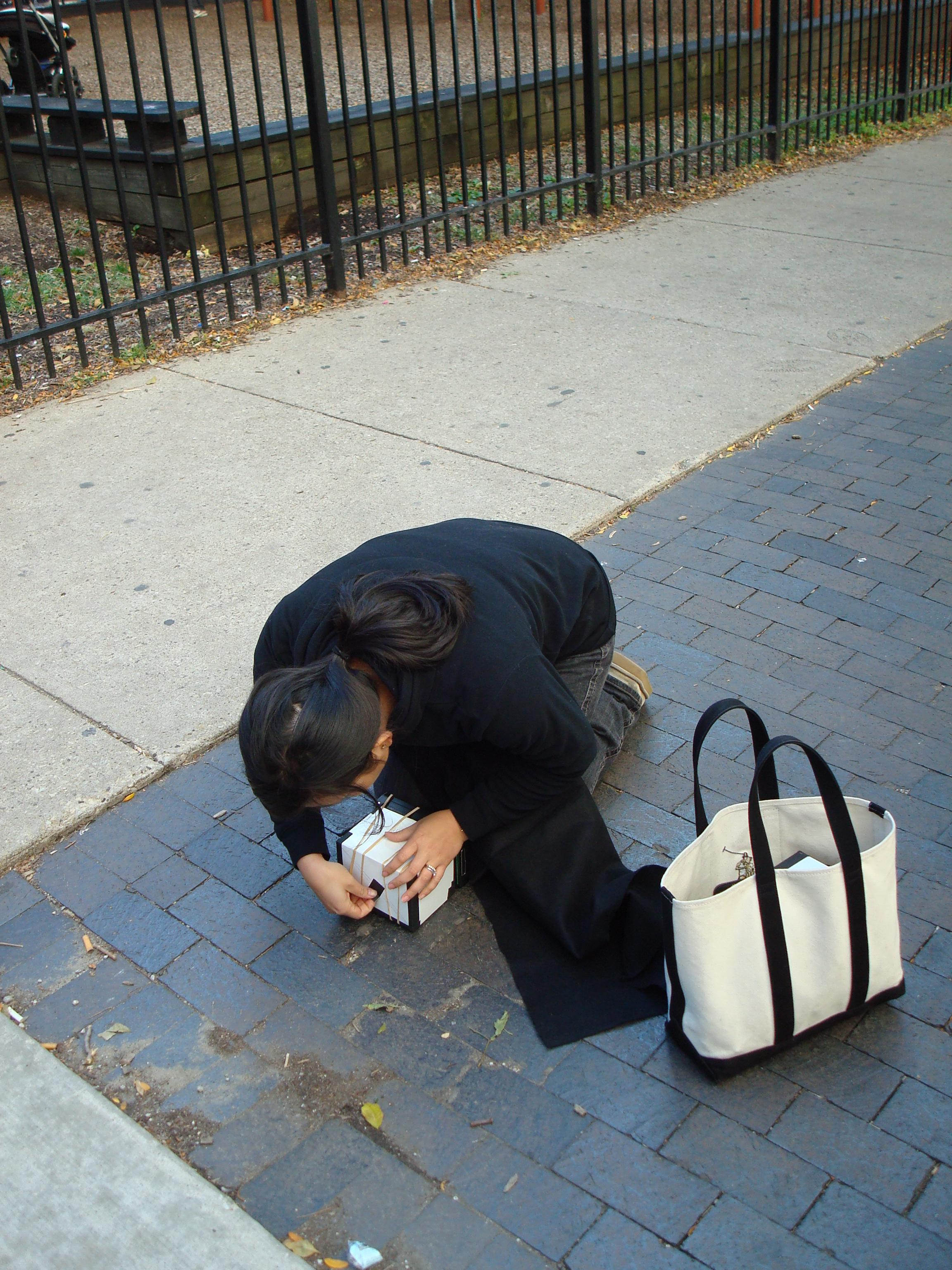 A person dressed in dark clothing kneels, hunched over a small white box and pulling out a small black tab.