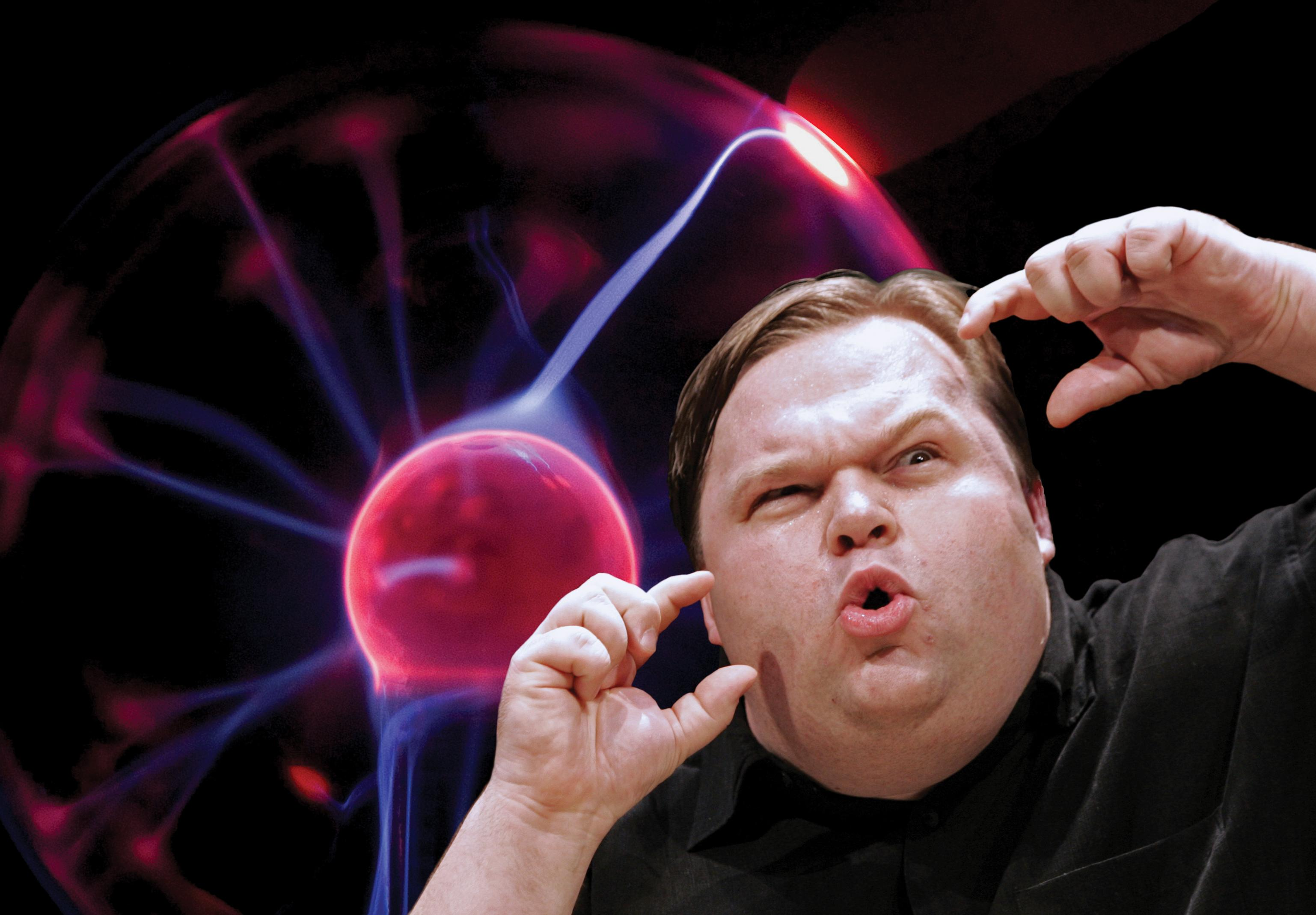 A heavy-set man makes an expressive face with one eyebrow raised and mouth puckered, holding his hands close to his face. Behind him is a clear glass globe emitting pink and purple electricity.