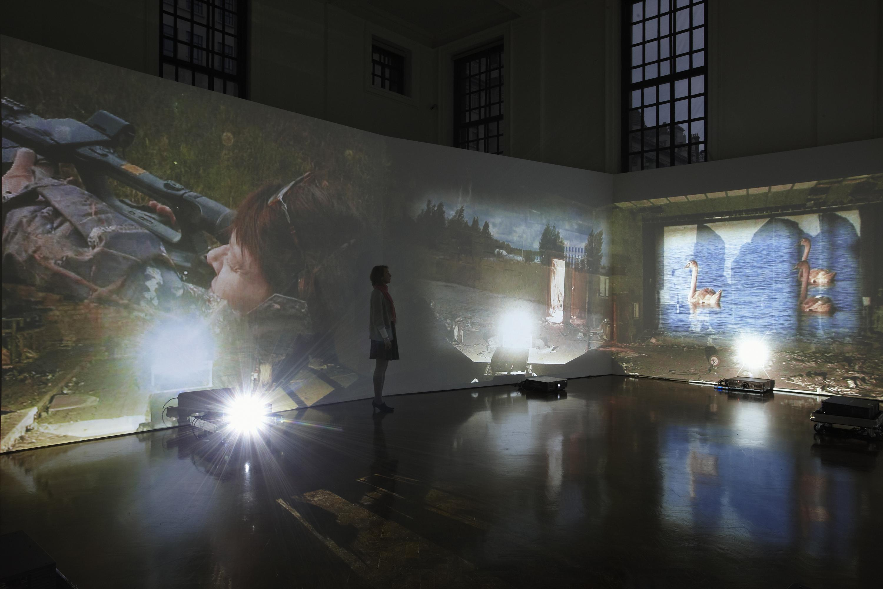 Installation view of a dark room with high ceilings that has three projectors on the floor projecting onto two gallery walls videos of birds swimming on the right and a female hunter aiming a gun on the left. A woman stands in the middle the installation watching the videos.