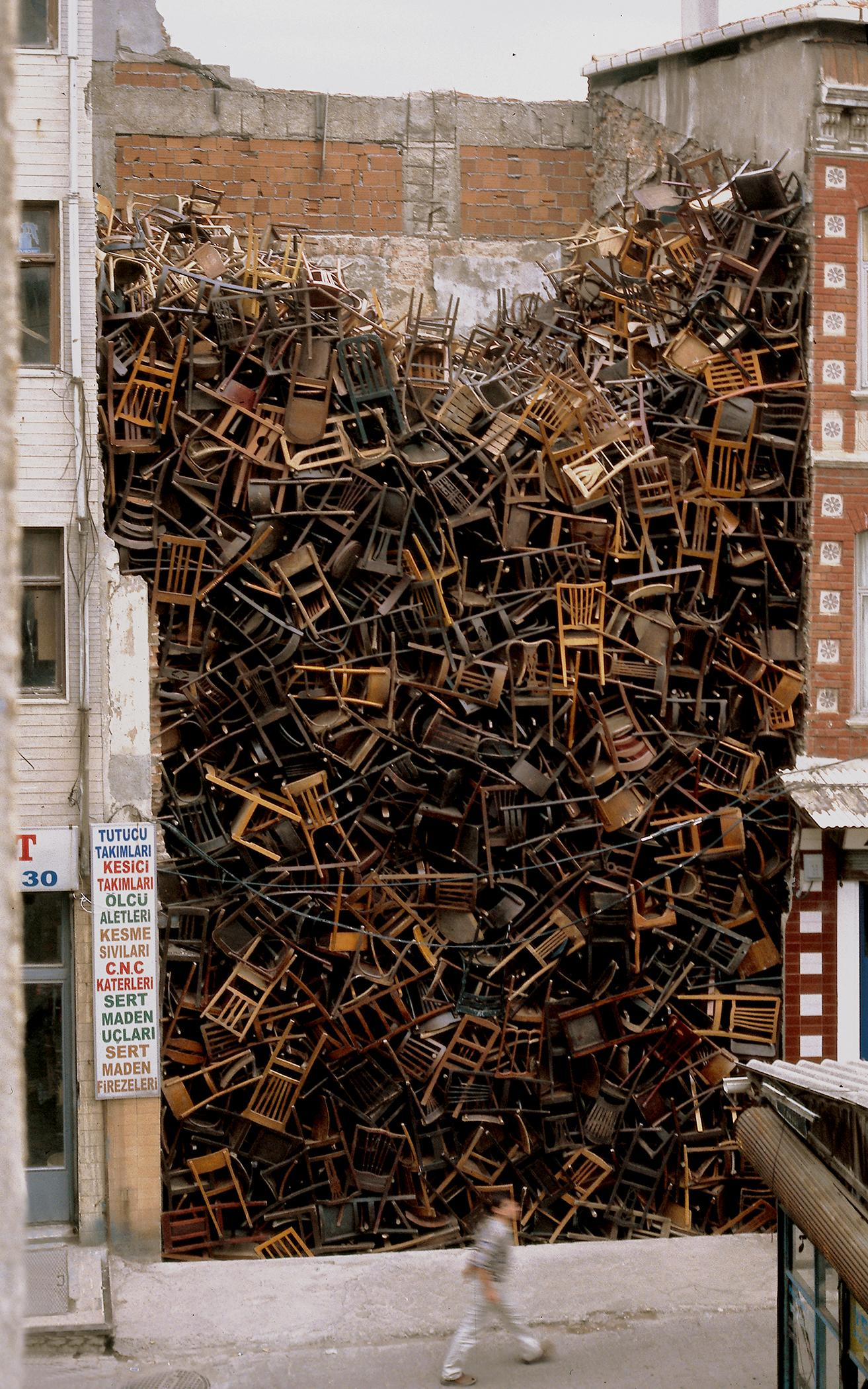A person walks by a massive pile of hundreds of wooden chairs placed between two buildings.