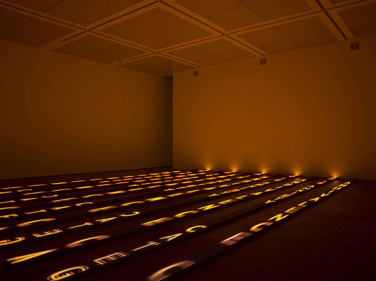 In a large darkened room, large letters are illuminated in yellow in vertical rows on the floor. These letters cast a warm glow over the room.
