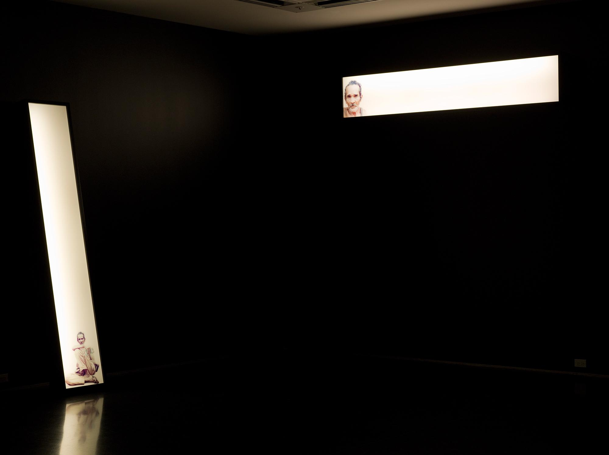 Two narrow glowing rectangles depicting a man illuminate a pitch-black room. The horizontal box on the right hangs high on the wall; the other leans vertically against the wall to the left.