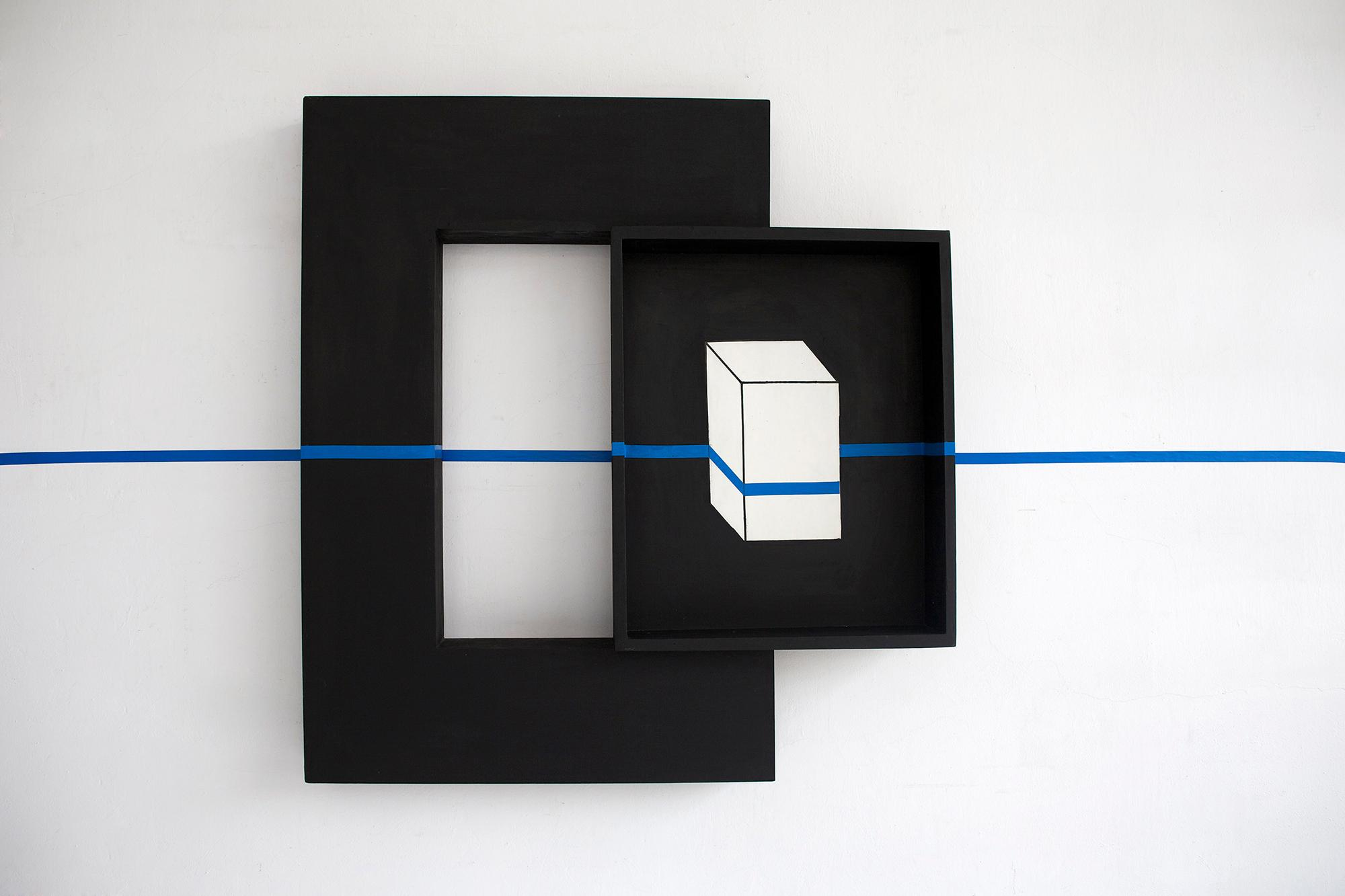 A black box containing an image of white box is mounted on the side of a thick black frame. The entire piece is intersected by a horizontal blue line, which appears to be painter's tape.