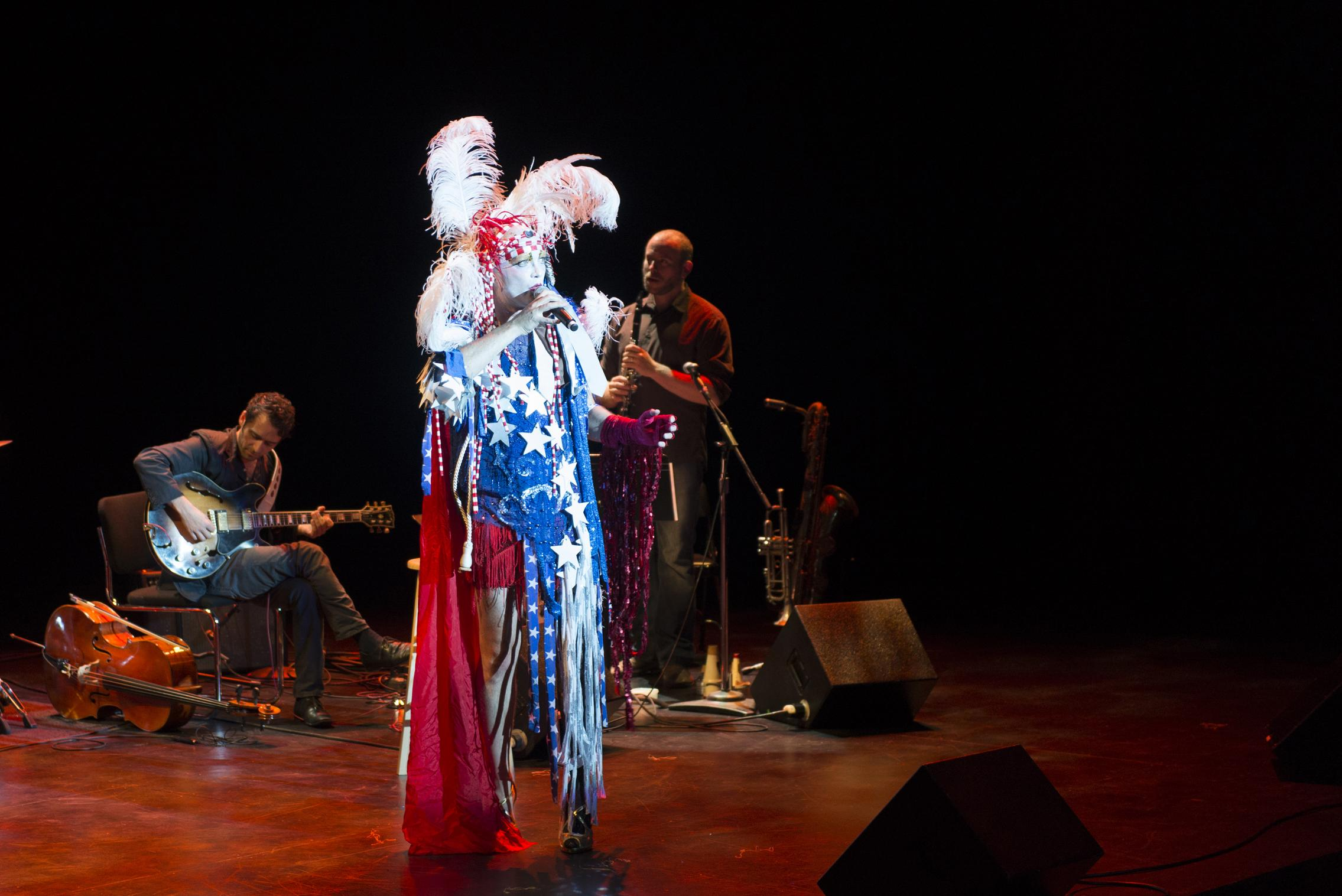 A person wearing a costume with a cape in red, white, and blue, and a feathered headdress sings on stage in the spotlight.