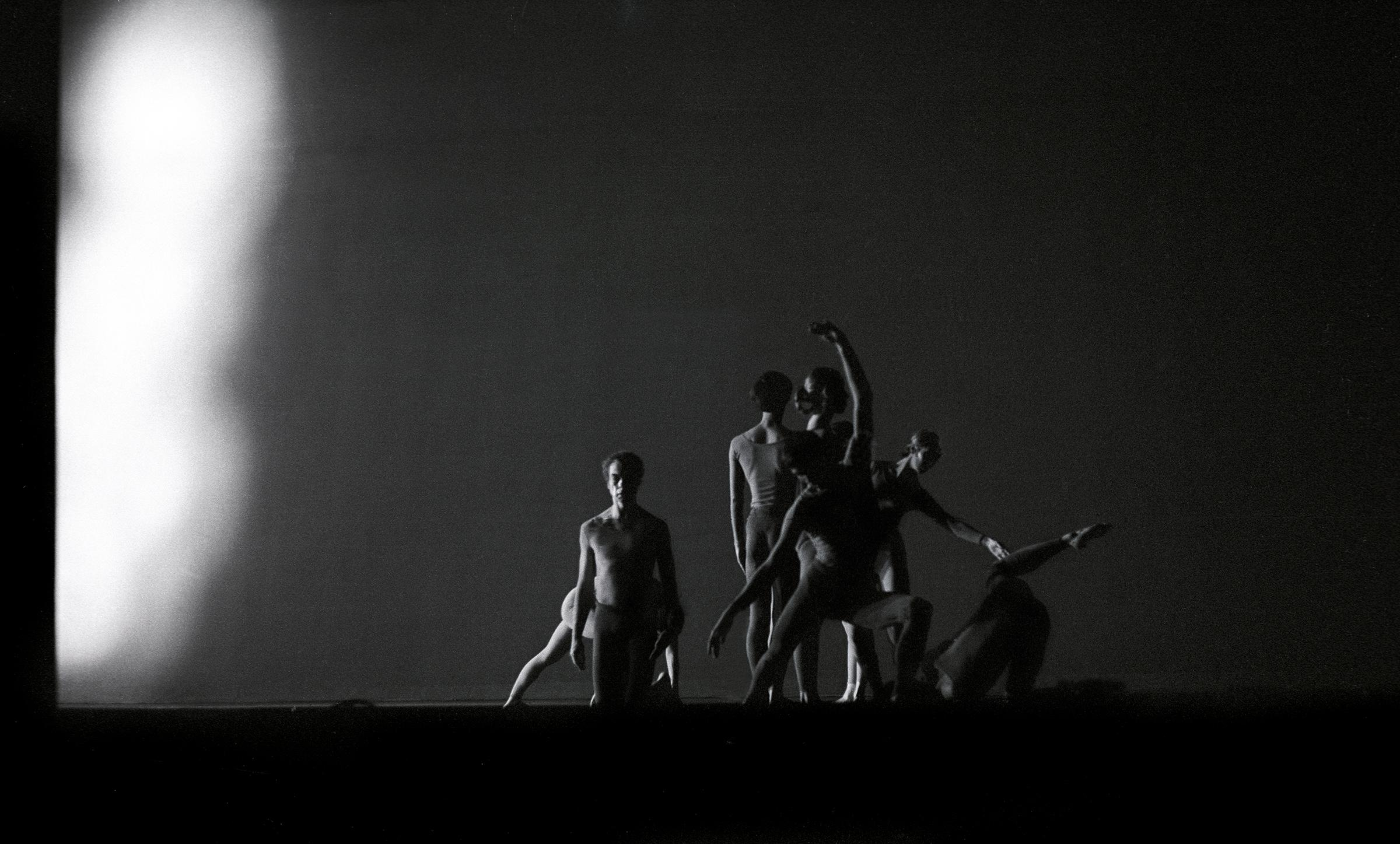 The black-and-white image captures a cluster of seven dancers holding poses against an empty background, with a strong light coming from the left.