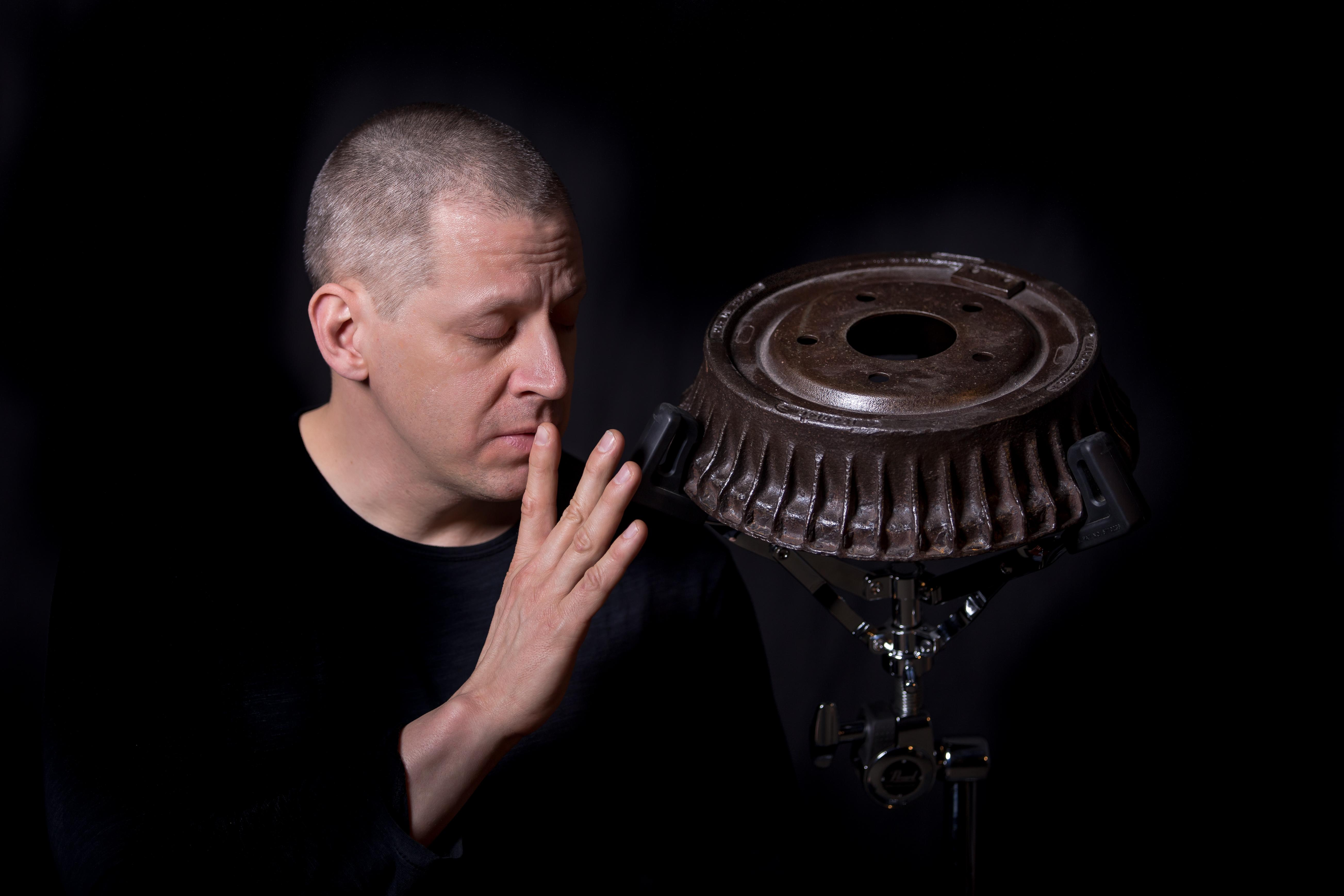 A pale-skinned middle aged man with closed eyes raises his fingers to his lips, turning toward the steel braking drum mounted on a drum stand next to him, against a black background.