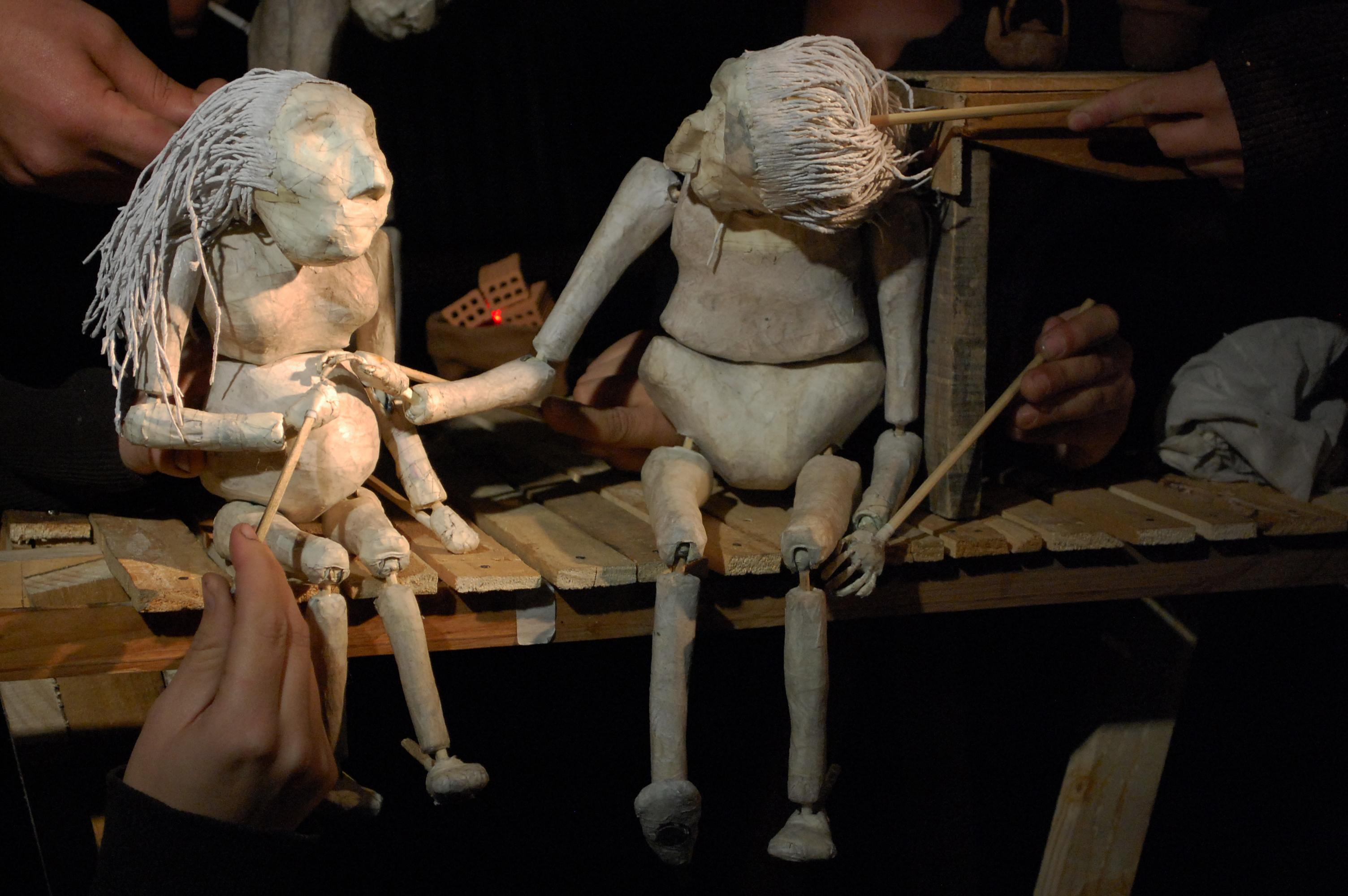 Two humanoid puppets hold hands while seated on a tiny wooden stage.
