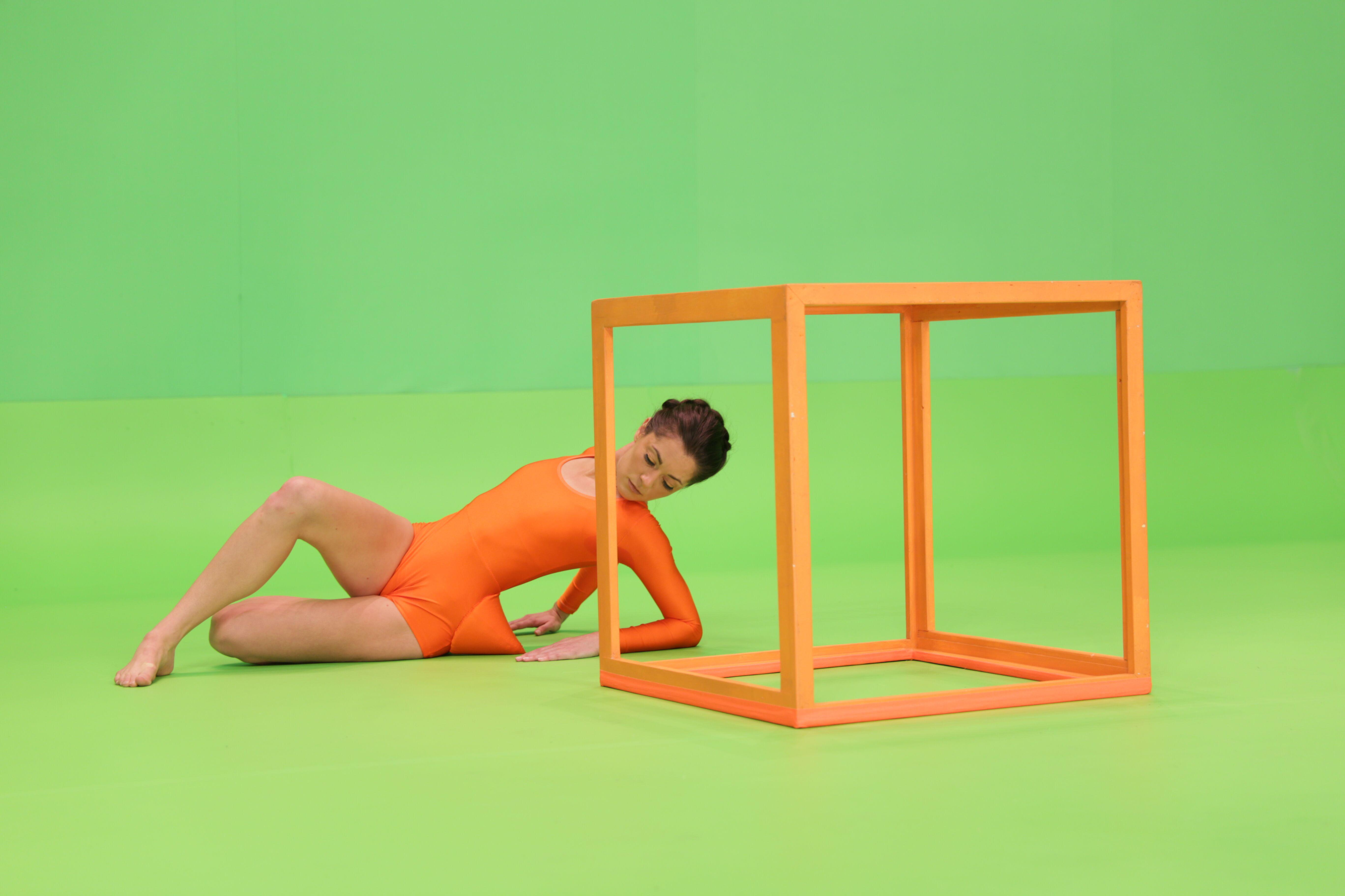 A dancer in orange leotard arches her back and rests on her elbows behind an open cube sculpture and against a bright green background. Her left hip is accentuated by a sharp cone in the same orange of her leotard.