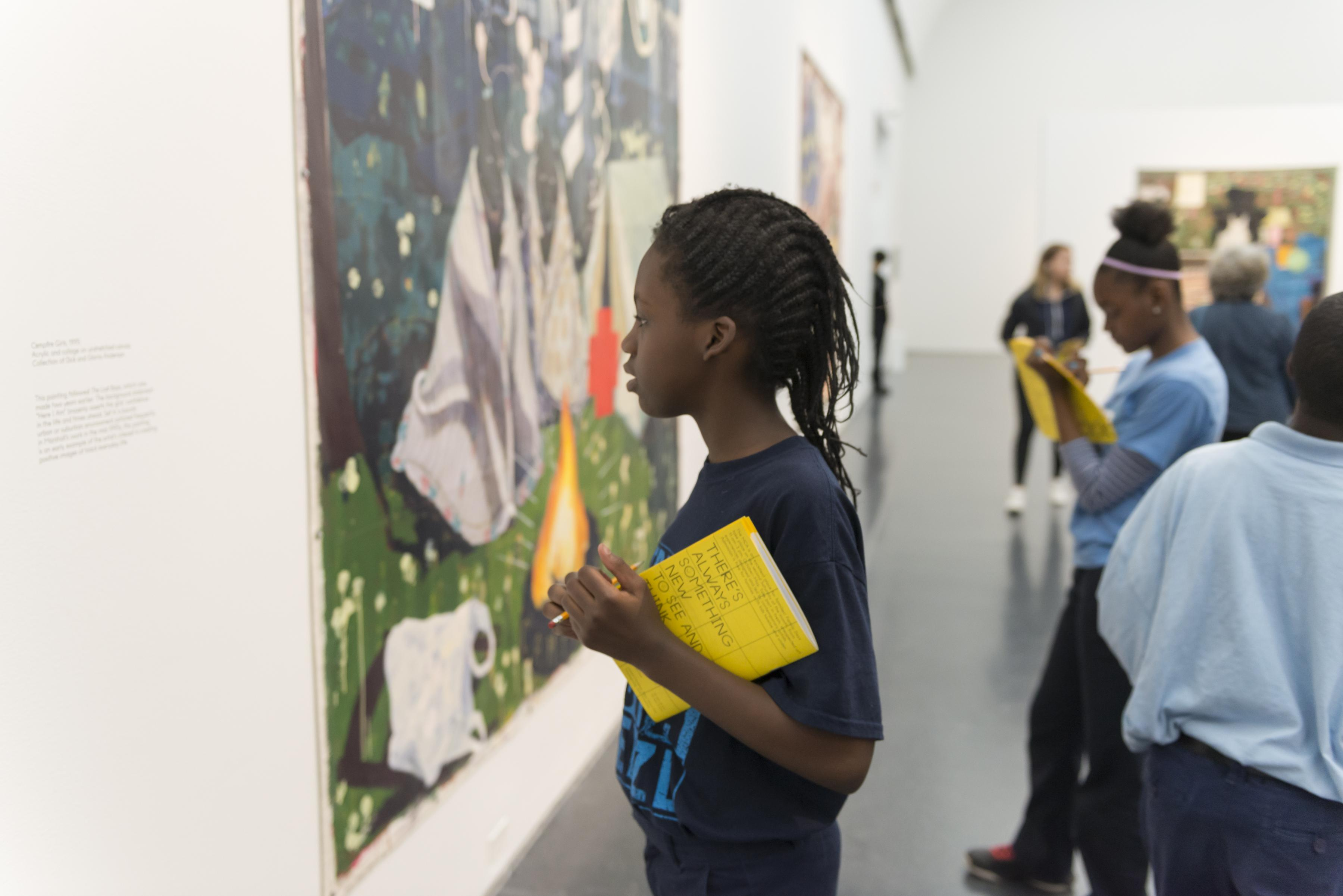 A young black girl holds a pencil and activity book in her hands while looking closely into the detail of a painting in a gallery.