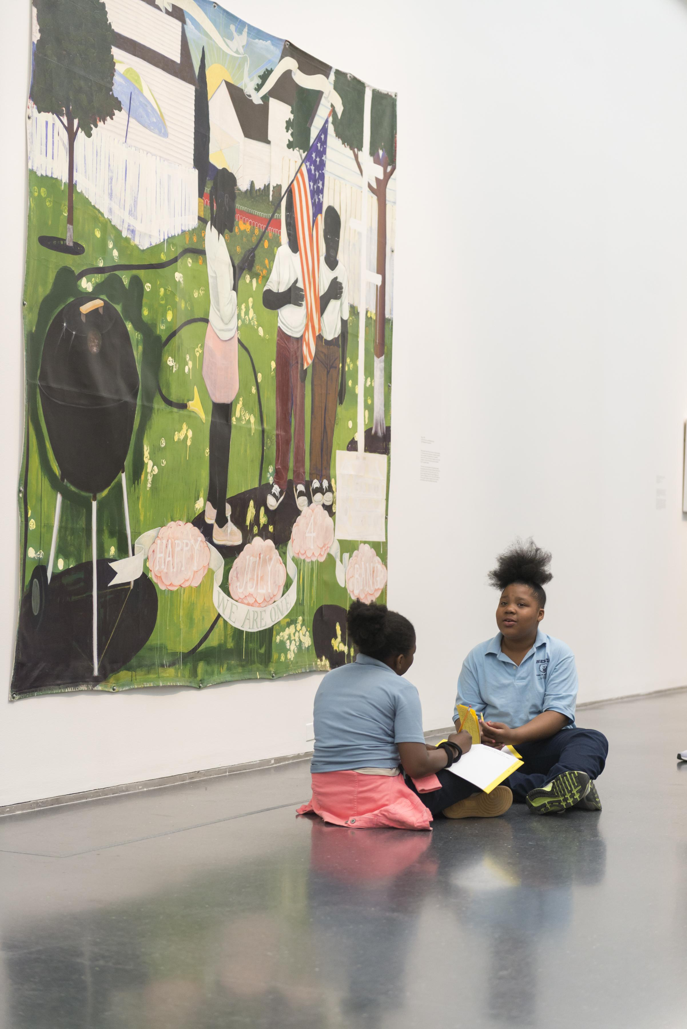 Two young black girls in school uniforms sit on the floor in front of a large painting while talking and writing in an activity book.
