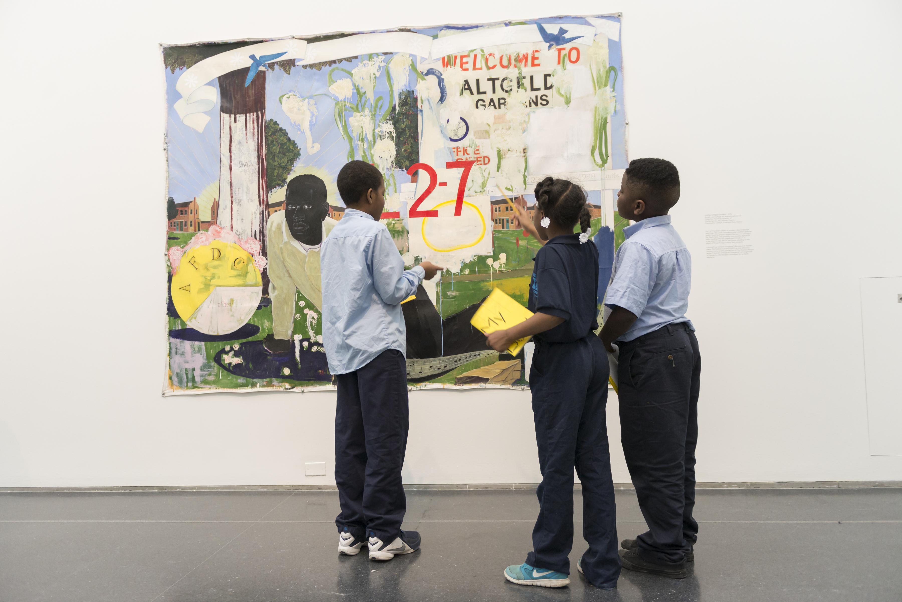 Three young black school children in school uniforms standing in front of a painting on a school tour.