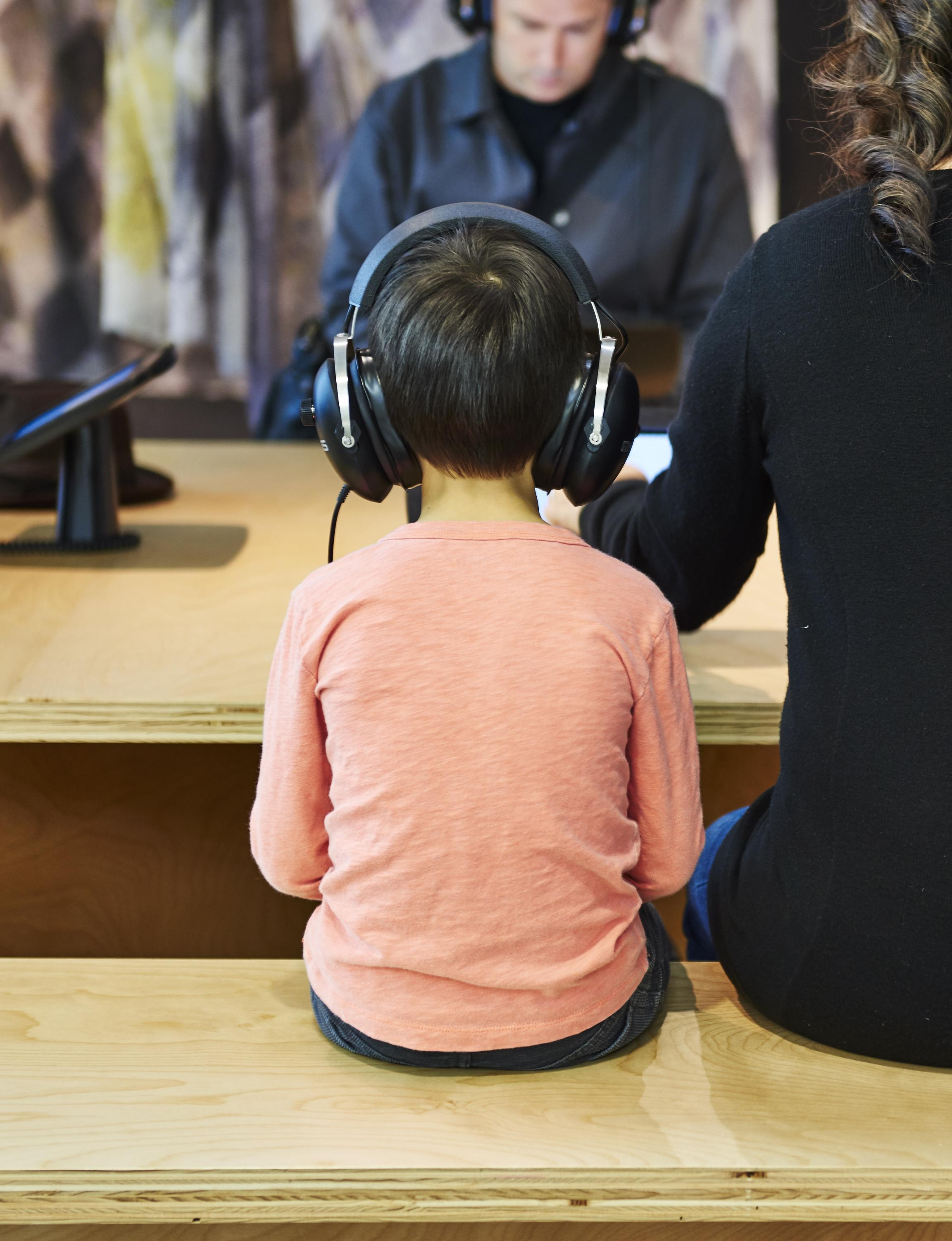A young child sits with his or her back to the viewer. The child wears oversized headphones and sits next to a woman at a wooden bench and table.