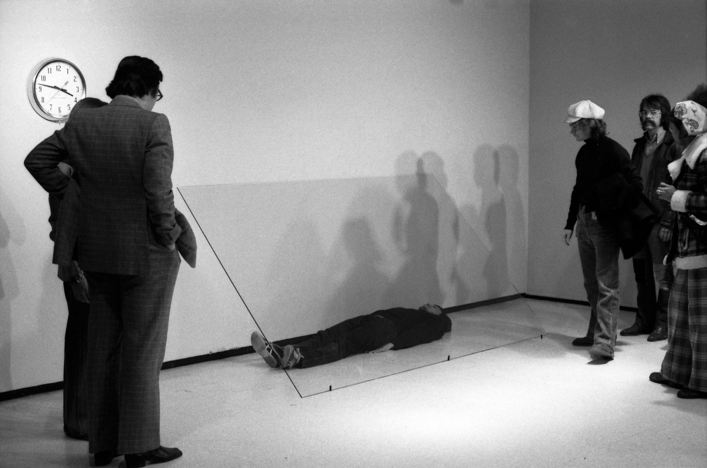 A group of museum visitors observe a man lying on the floor underneath a sheet of glass.