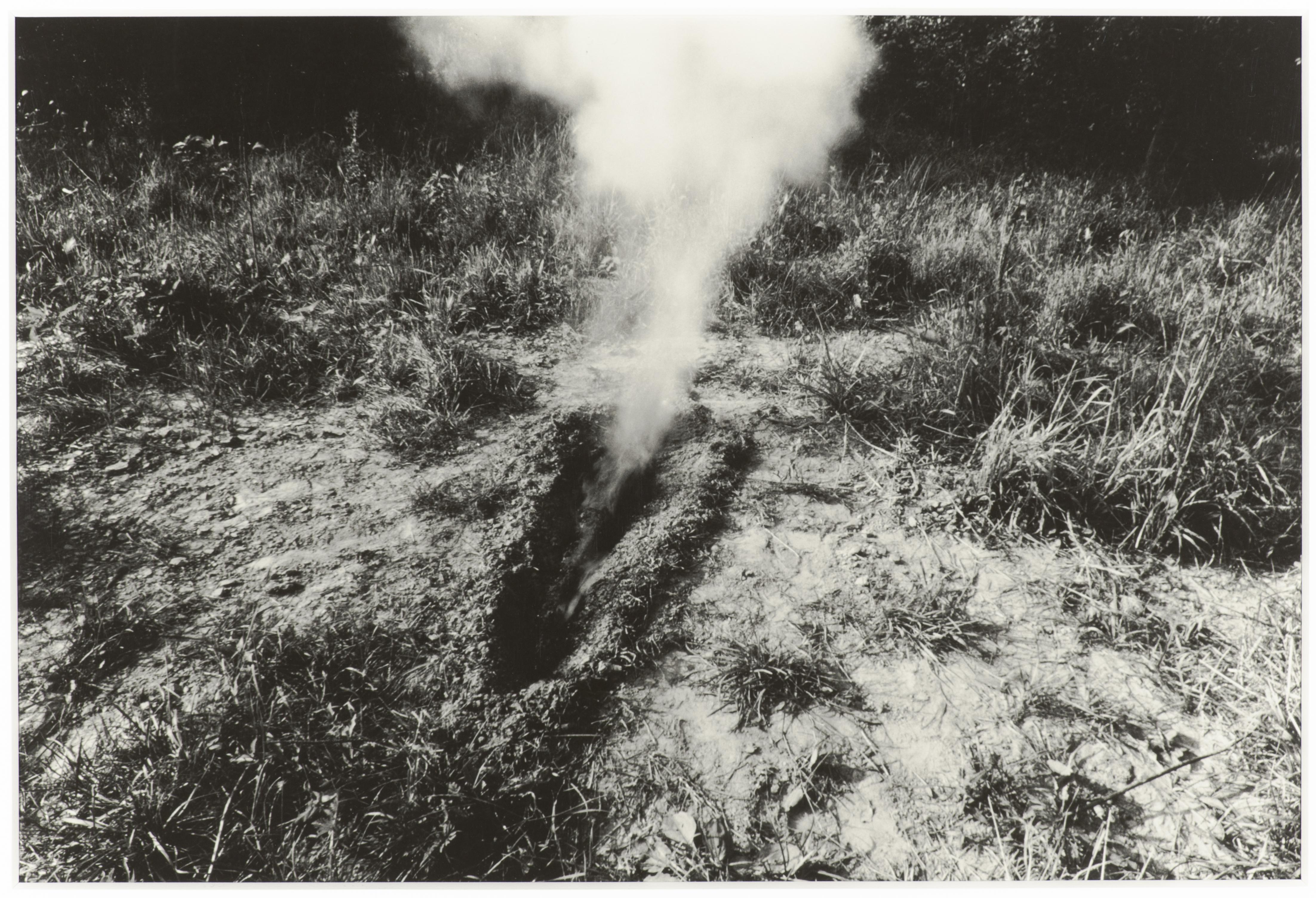 A black-and-white photo captures smoke billowing from a body-sized trench in a clearing with weeds and trees in the horizon.
