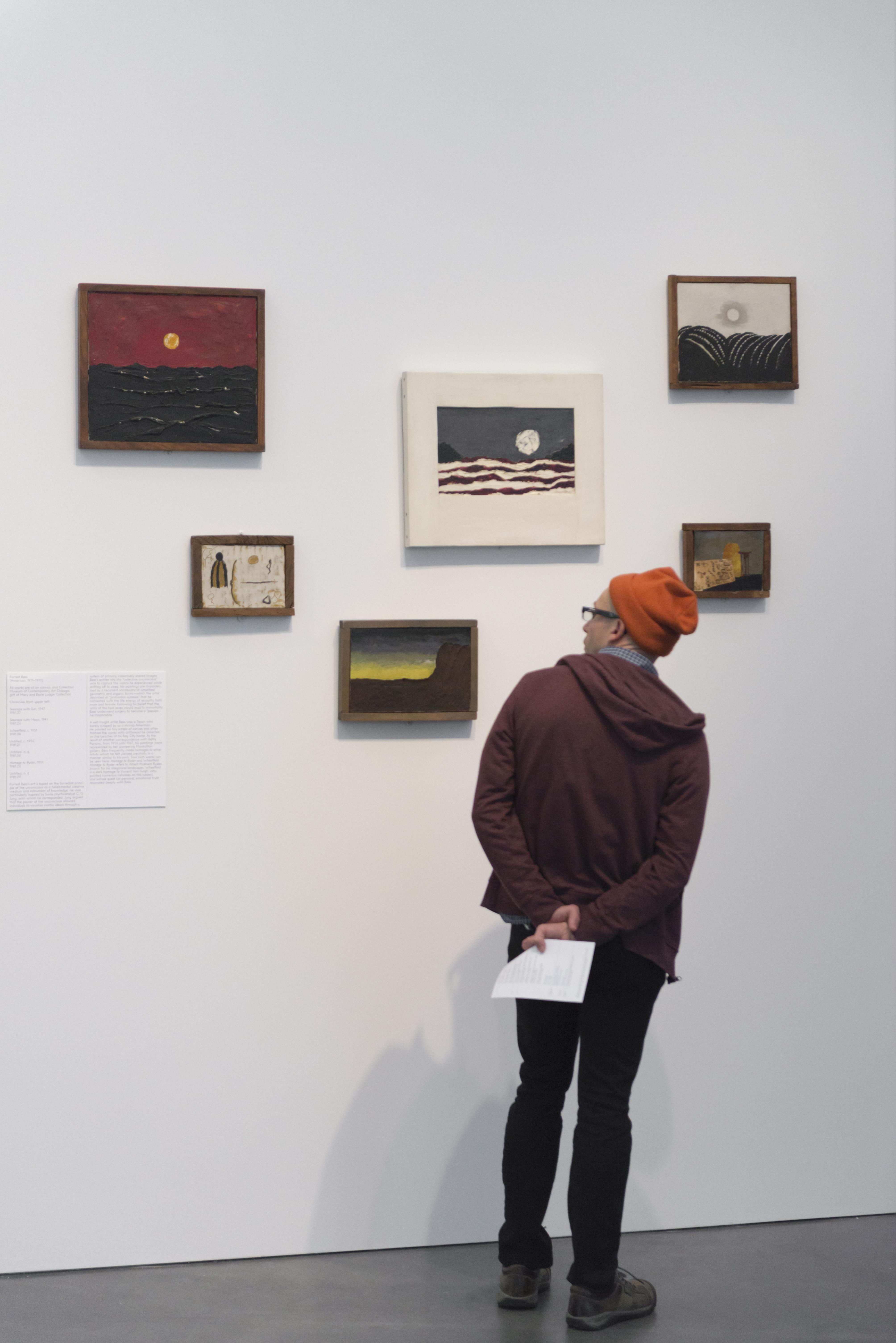 A person wearing a hoodie and beanie faces six small and medium sized paintings on a gallery wall.