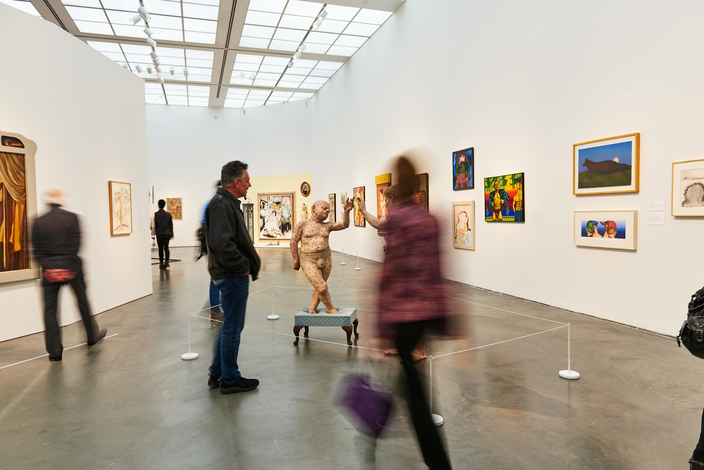 Several visitors look at paintings and sculpture in a gallery whose curvilinear walls draw viewers closer to its center.