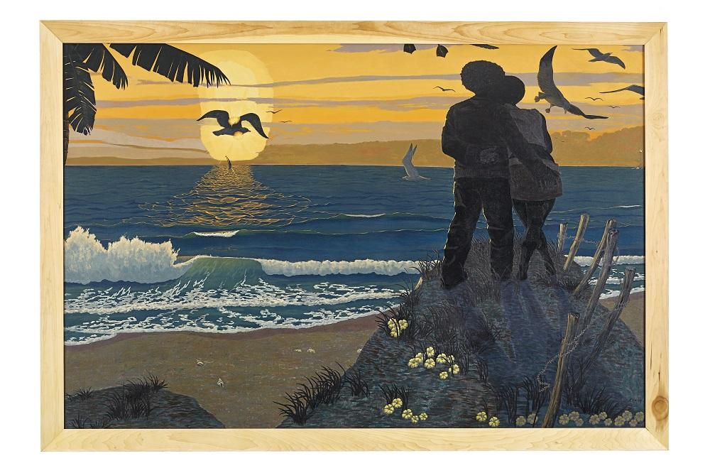 Two people stand with arms around each other while looking at a soft orange sunset on the beach. Waves hit the shore as birds fly above.