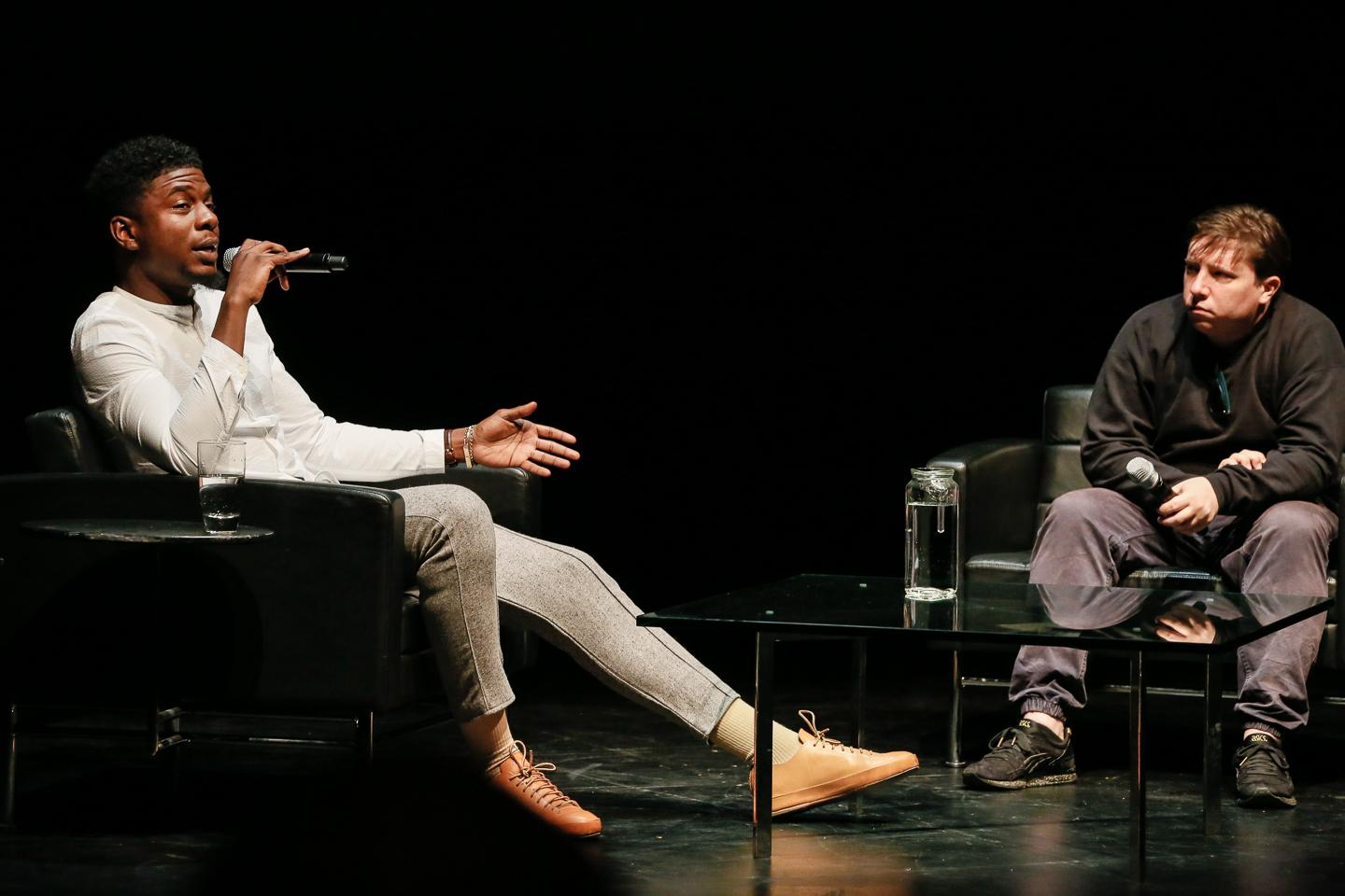Against a black backdropped stage, a man reclines in an armchair speaking into a microphone while another leans in to listen, waiting his turn.