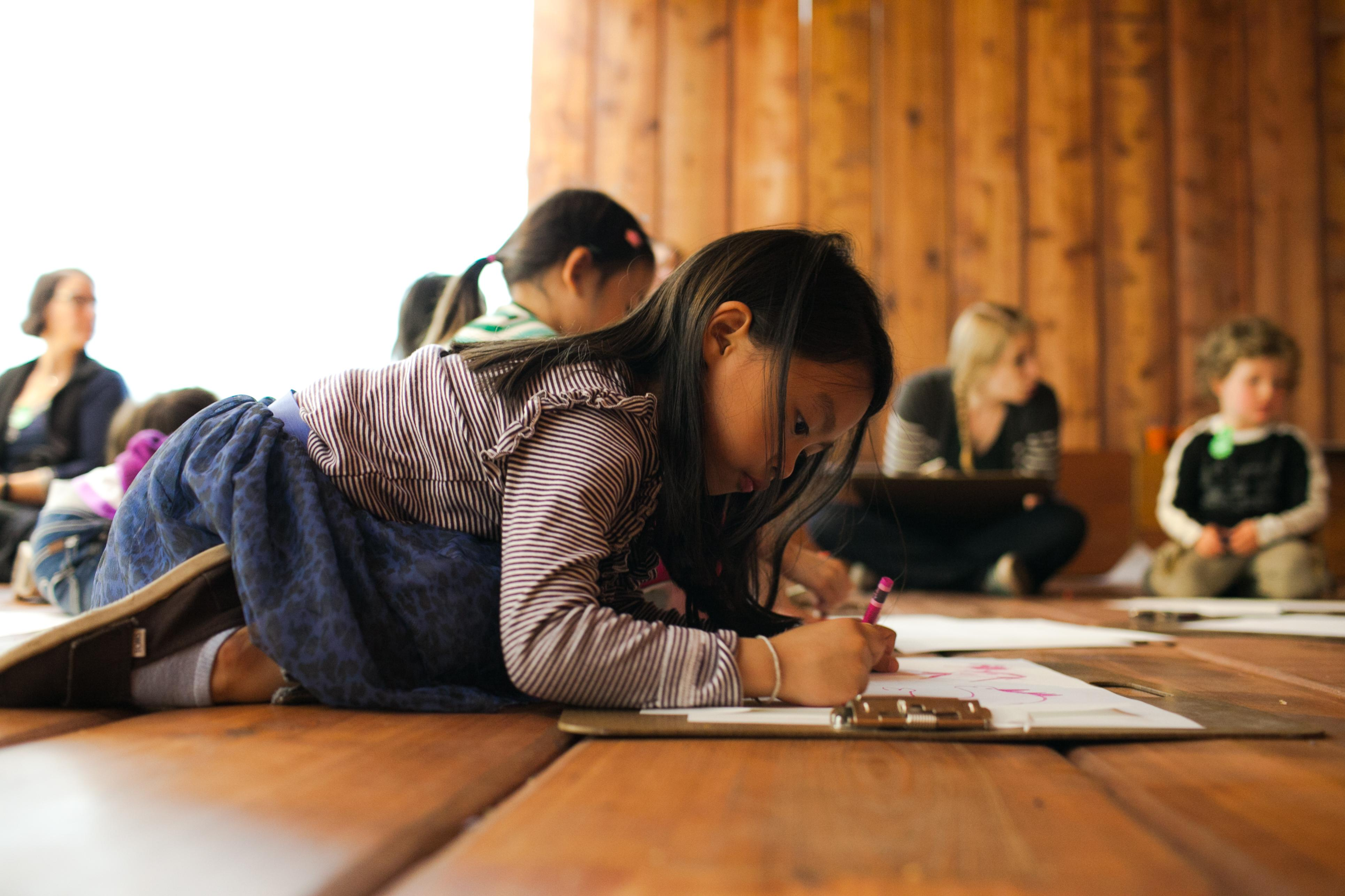 A young child lays on the ground to draw on a clipboard with a crayon.