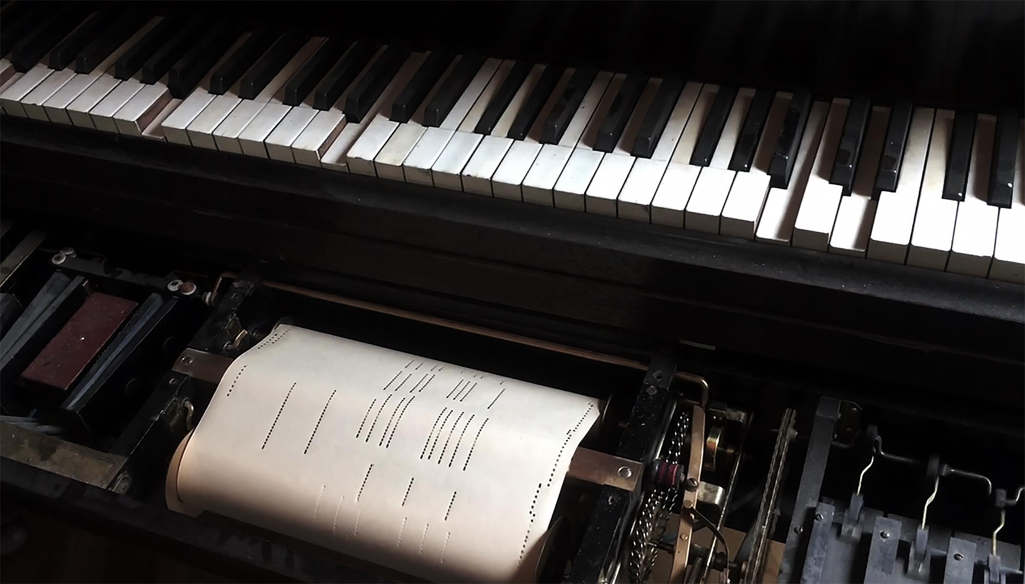 A close-up of a player piano keyboard captures the roll of sheet music mid-song.