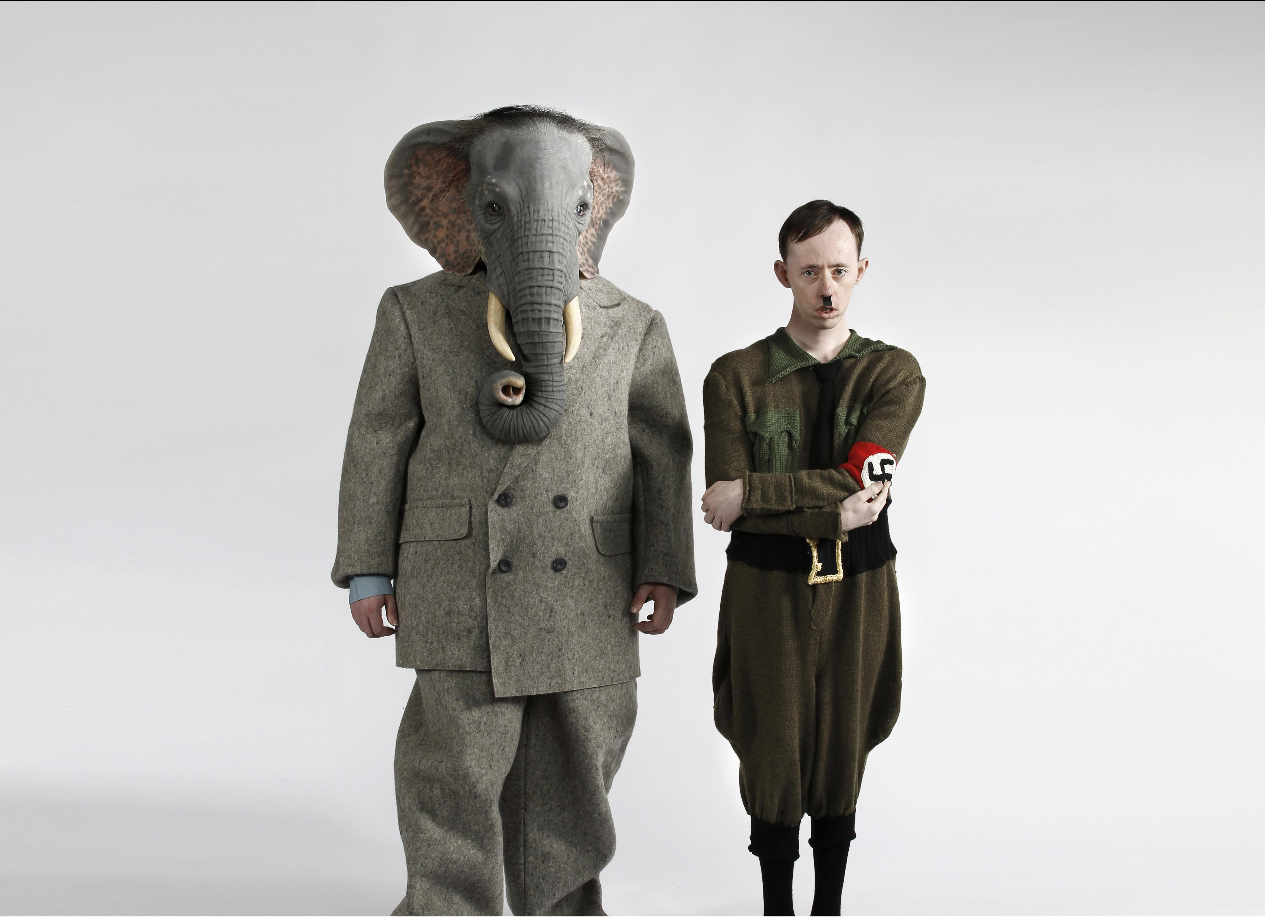 A person with a head like an elephant wears a gray business suit and stands beside a person in a nazi uniform who resembles Adolf Hitler.