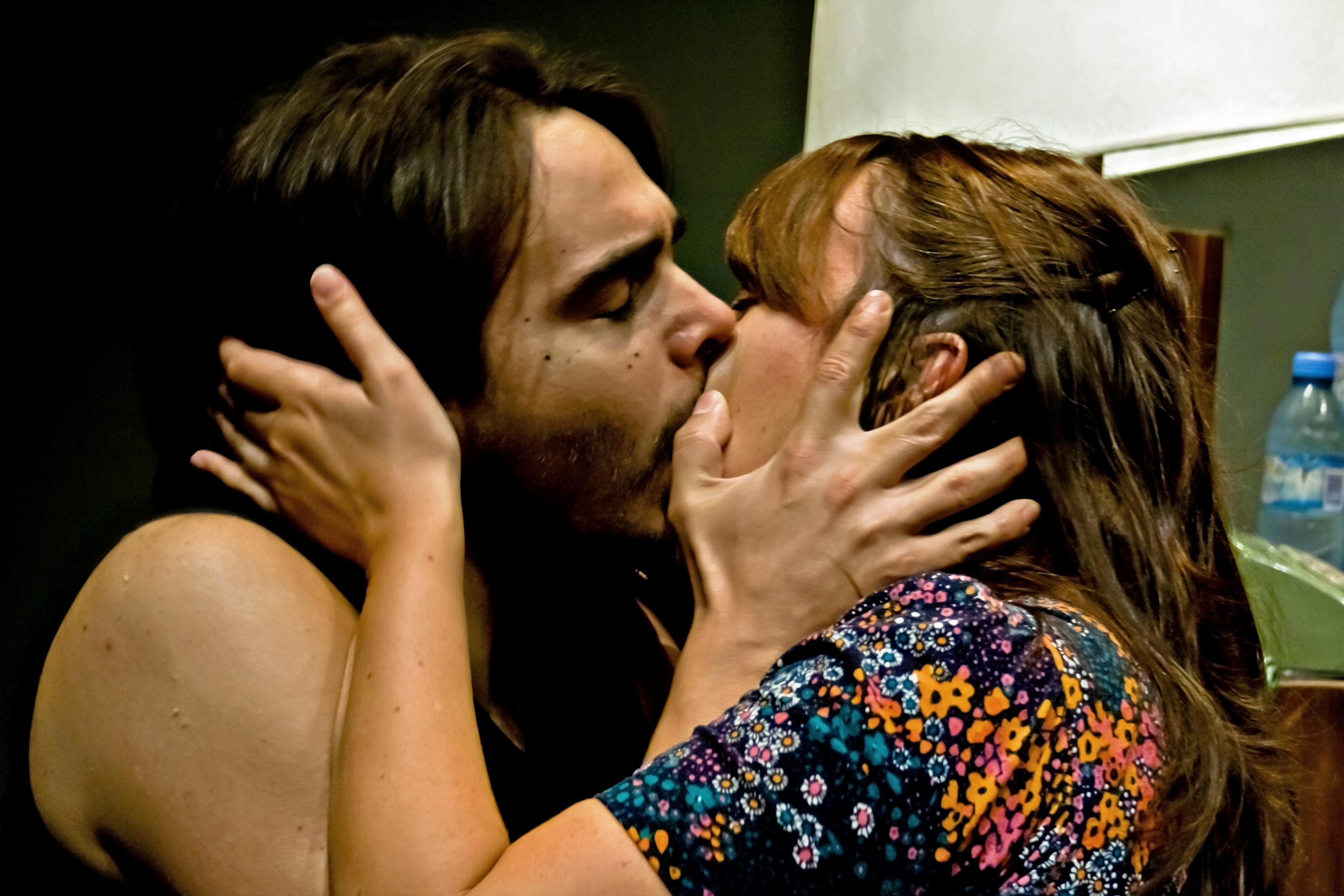 A man and a woman hold each others' heads while kissing passionately.