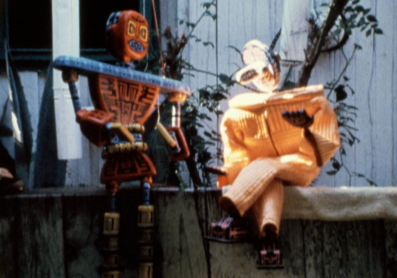 Two orange robots sit outdoors facing each other as if in conversation.