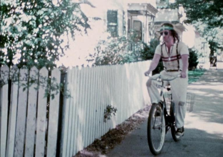 A grainy video image of a person riding a bike in front of a white picket fence.