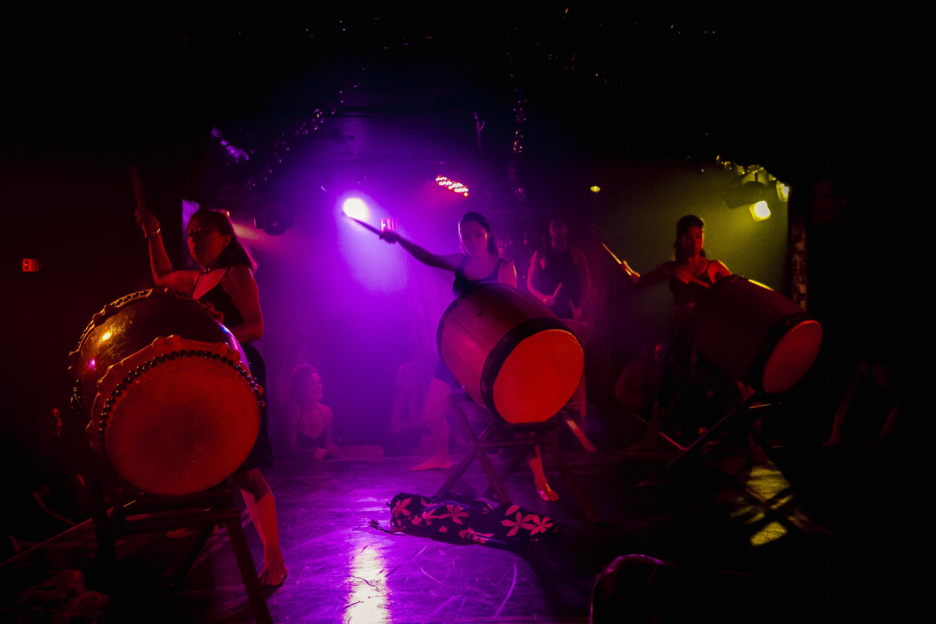 Three huge drums are held by women holding drumsticks high, they are illuminated in a dark space by pink, red, and yellow lights.