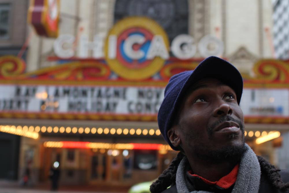 A young black man wearing a hat in front of the Chicago Theater looks up.