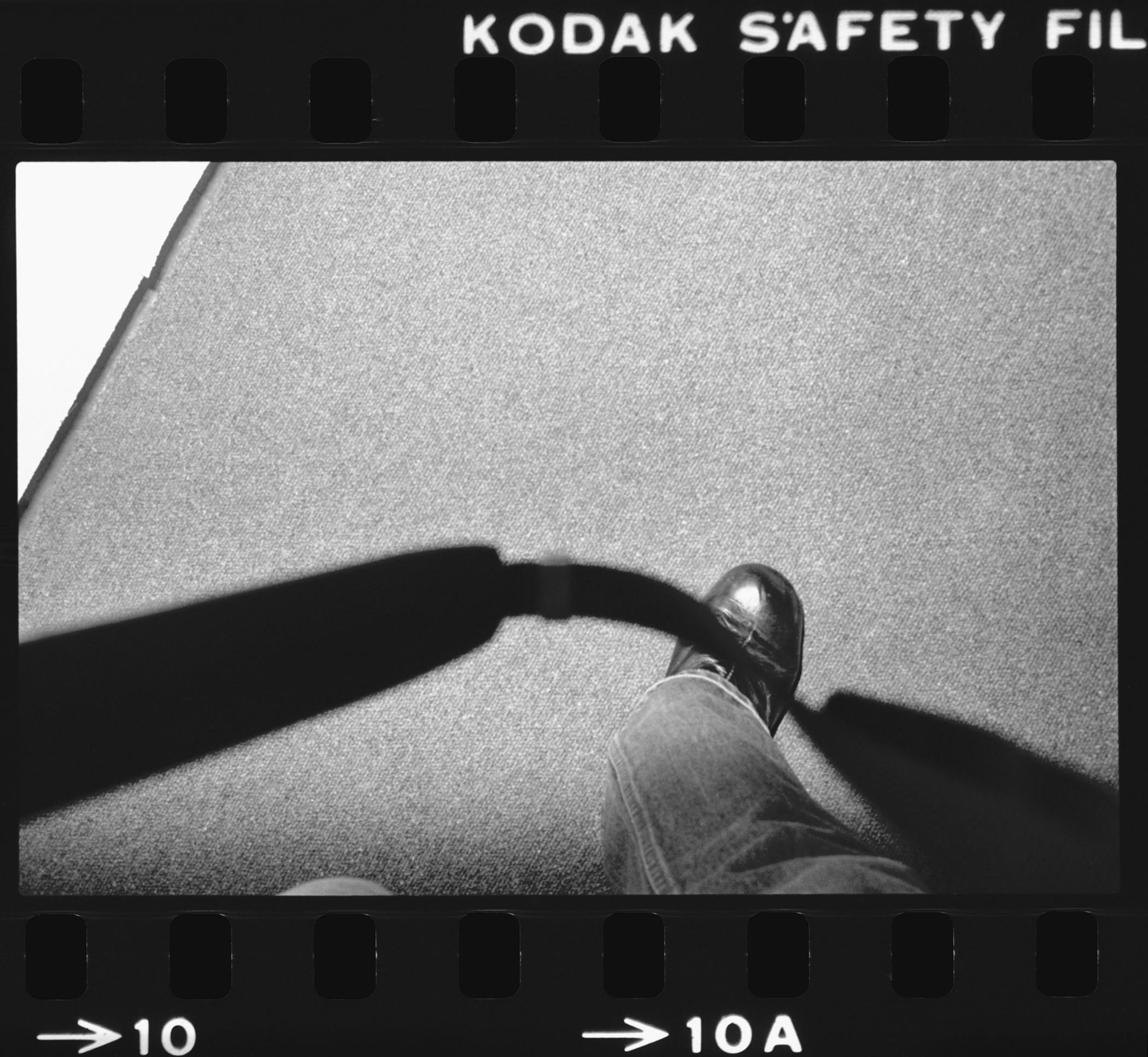 A 35 mm black-and-white film frame depicts a camera strap looping down toward the lower part of a right leg clad in denim as the person raises their foot to take a step.