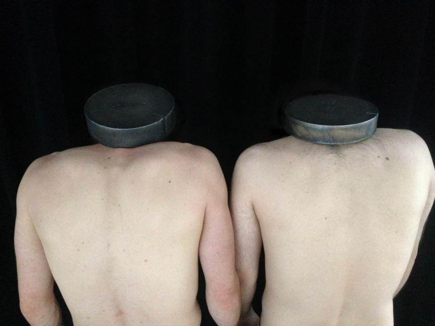 Photograph of two nude headless male torsos seen from behind against a black background. Round metal discs rest on their shoulder in place of heads.
