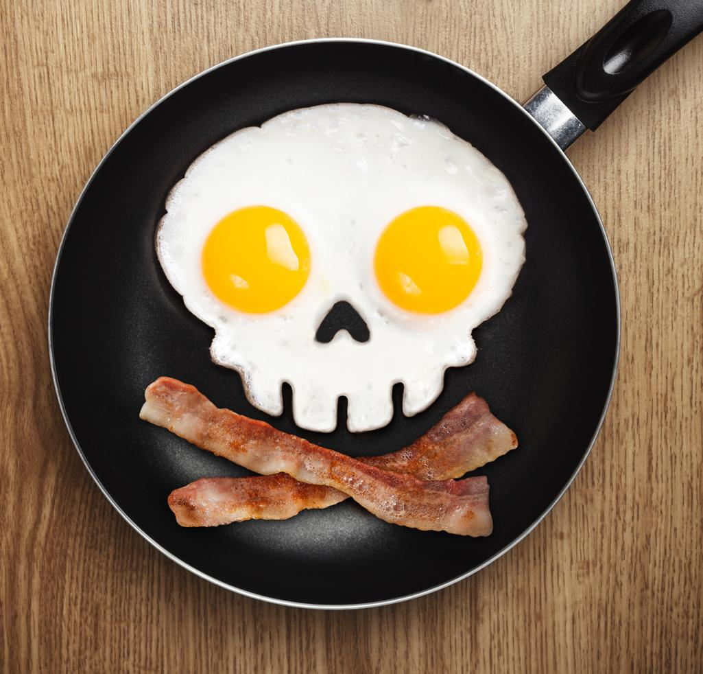 A black frying pan serves up a skull and crossbones made from eggs and bacon.